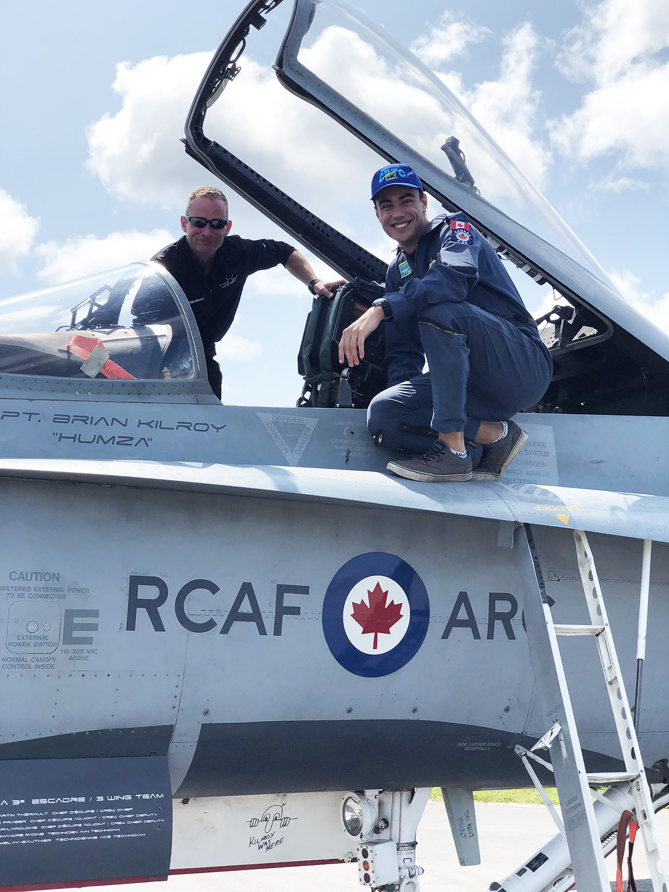 Cadet Warrant Officer First Class Nicholas Lourens (right) and Master Corporal Mike Williams crouch on opposite wings of the 2019 Canadian Armed Forces Demonstration Hornet. PHOTO: Lieutenant Becky Major