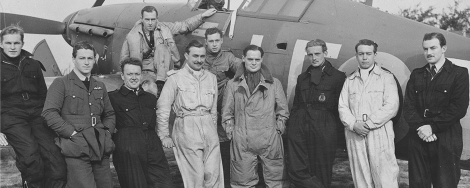 slide - A group of men in various uniforms stand in front of a single propeller aircraft.