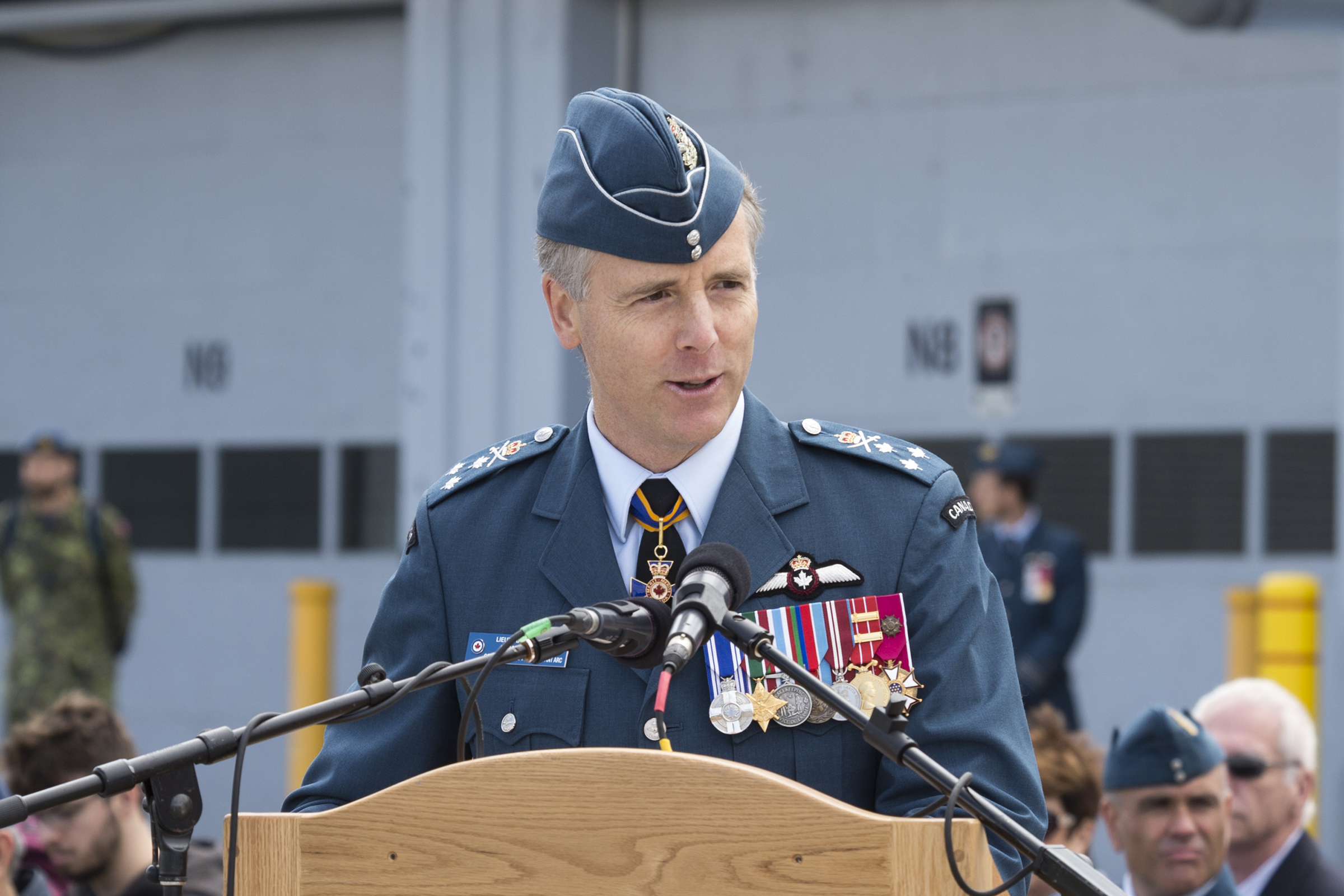 A man wearing a military uniform stands behind a lecturn speaking into a microphone.
