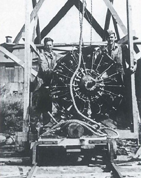 "Warrant Officer James Doan (left) and Corporal David Rennie stand with the engine change rig at the RCAF seaplane base at Lac Mégantic near the Québec–Maine border. The trolley below them would be run down the rails to the beached and engineless Delta. This is likely the last photograph taken of the two airmen. PHOTO: From ""Mystery Plane Found in New Brunswick"" by James Cougle"