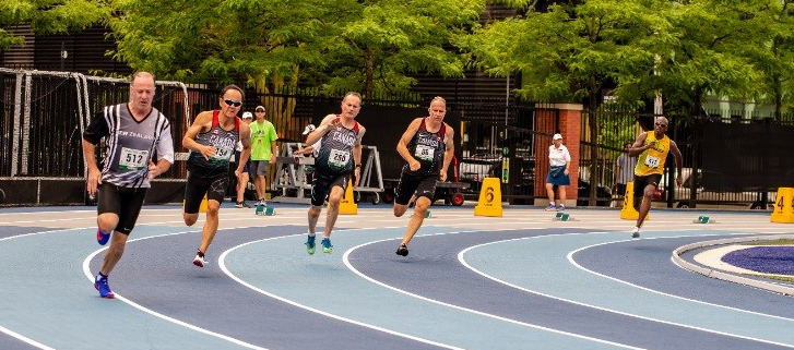 Five men in running gear round a corner on a track.