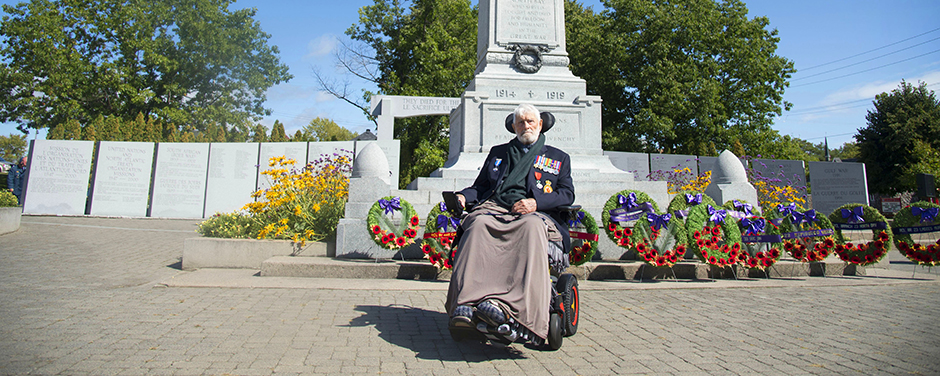 slide - An elderly man wearing a dark jacket displaying many medals sits in a wheelchair in front of a large monument topped by a bronze soldier and fronted by wreaths on stands.