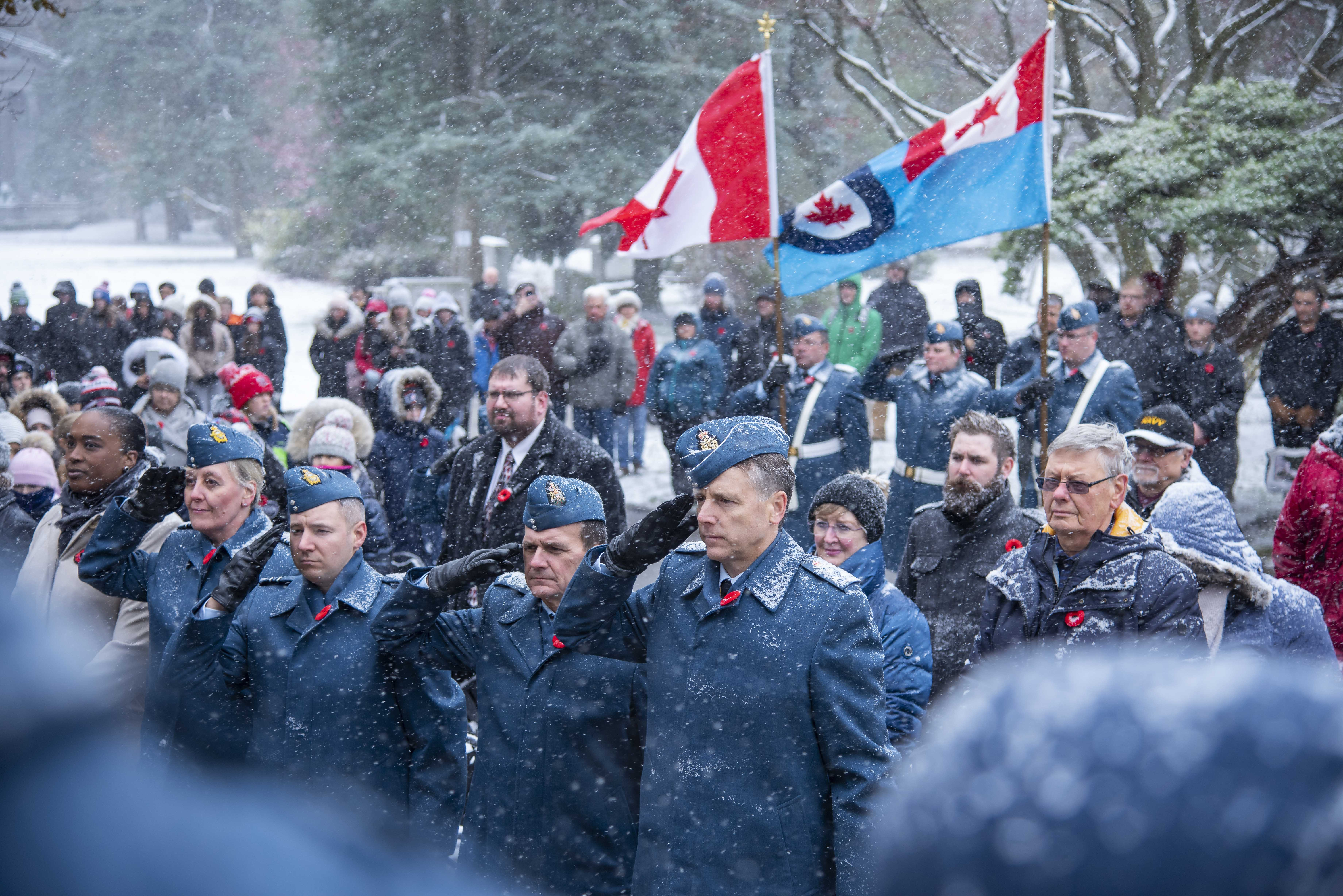 Four people dressed in Air Force uniforms salute, as snow falls. They are surrounded by a crowd of people.