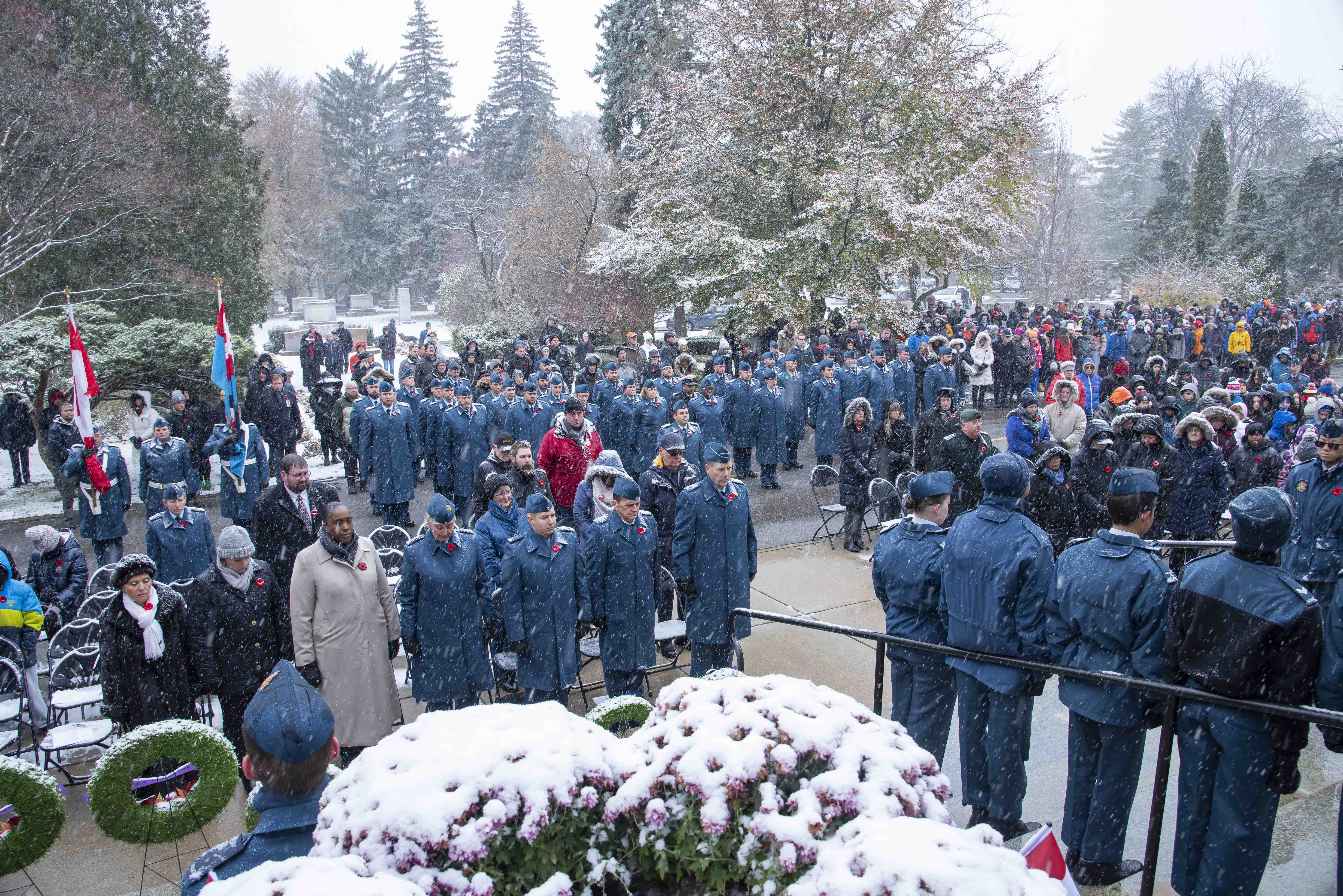 A large crowd of military personnel, veterans, youth and other members of the public stands in the falling snow during the 2019 Remembrance Day ceremony held at the mausoleum where Wing Commander William Barker, VC, is interred in Mount Pleasant Cemetery, Toronto. PHOTO: Corporal Lynette Ai Dang, BM10-2019-0359-026