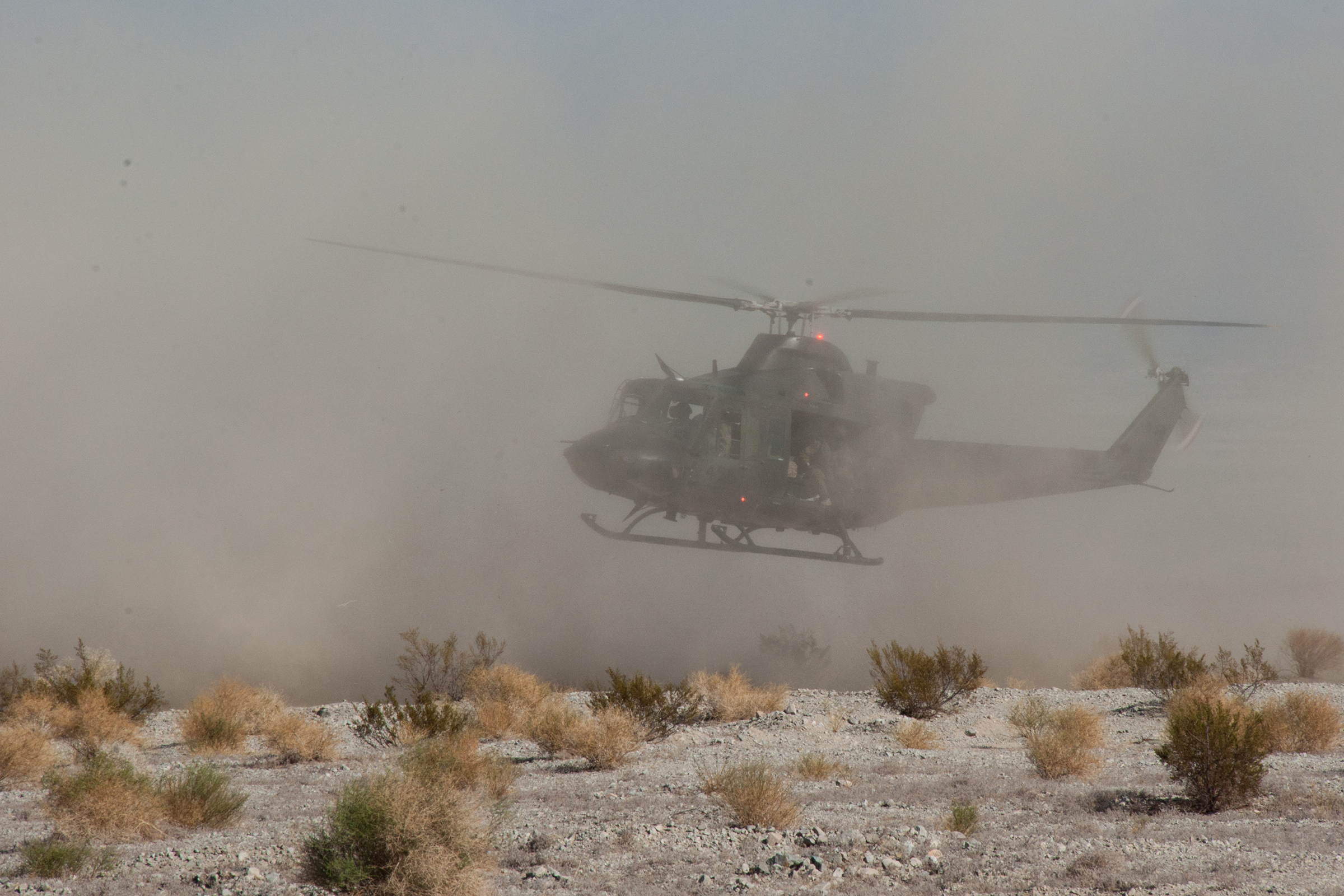 A military helicopter flies very low above a desert landscape, surrounded by dust.