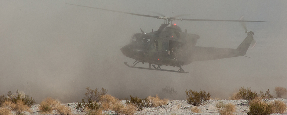 slide - A military helicopter flies very low above a desert landscape, surrounded by dust.