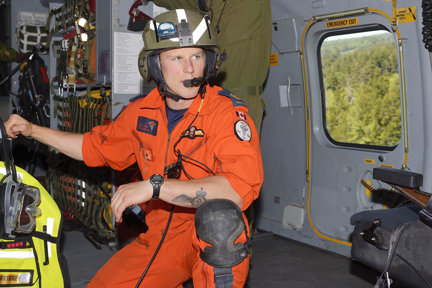 A man wearing orange coveralls and a green helmet with a communications package and a beacon sits in the cargo area of an aircraft in flight over heavily forested land.