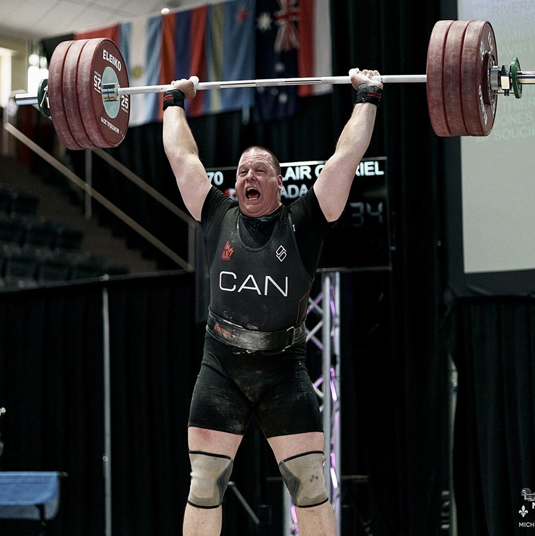 "A weightlifter wearing black shorts and t-shirt, and a vest reading ""CAN"", holds a bar with three weight plates on each end above his head."