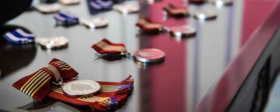 slide - Various medals, with ribbons attached, are lined up in rows on a table.