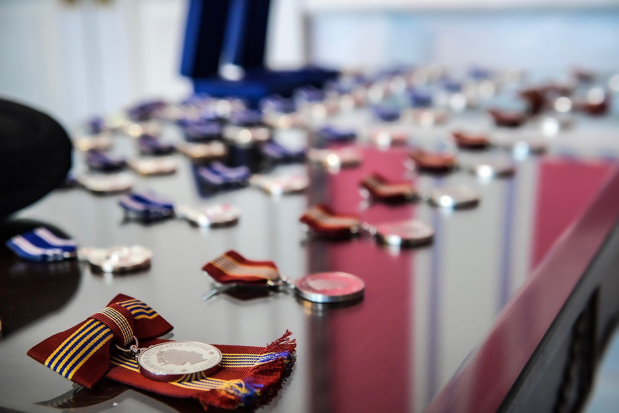 Various medals, with ribbons attached, are lined up in rows on a table.
