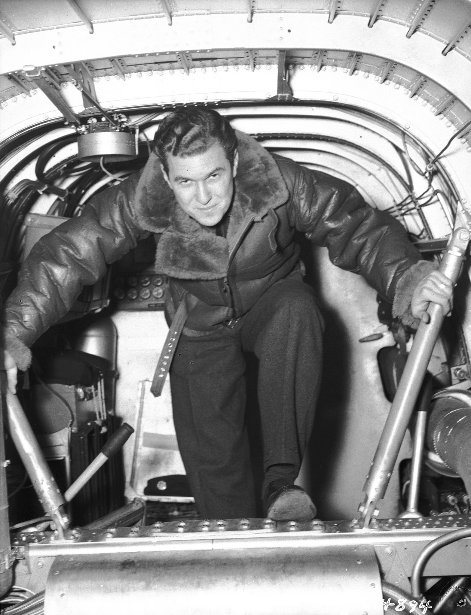 "Pilot Officer Jack Watts climbs out of a four-engine bomber at an RAF station in England on December 17, 1941. The original caption reads: ""Jack is an observer with the RCAF, trained at Toronto, Malton, Jarvis and Rivers. He is an 'old boy' of Delta Collegiate, where he was outstanding in basketball, track and football. Previous to the war he worked in the Firestone Plant, Hamilton. He has had nine trips over enemy occupied territory."" PHOTO: DND Archives, PL-4894"