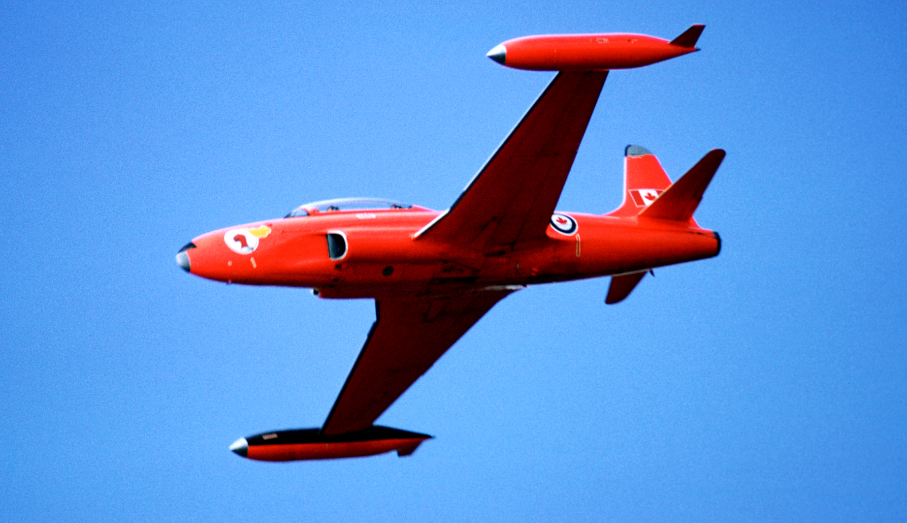 A red aircraft in flight.