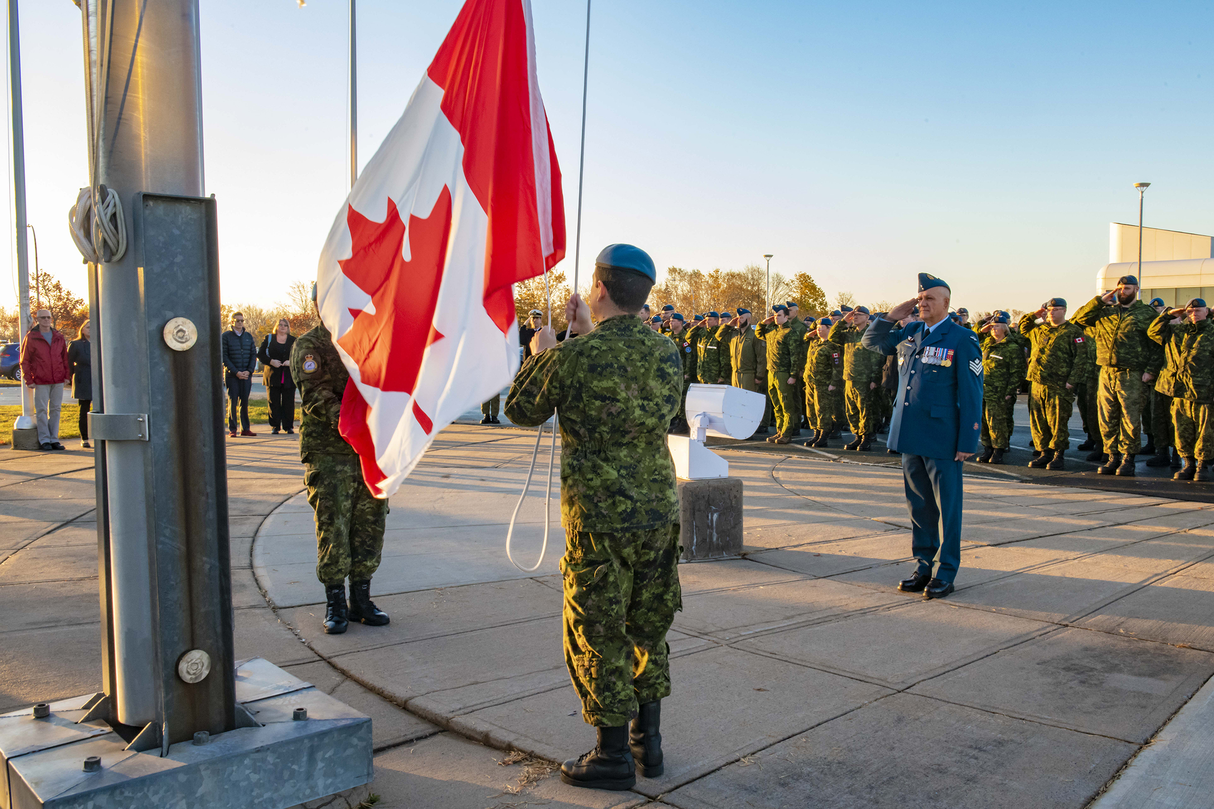 In the foreground, a person wearing a camouflage pattern uniform raises a Canadian flag, while a man wearing an RCAF dress uniform salutes and additional personnel in the background salute.