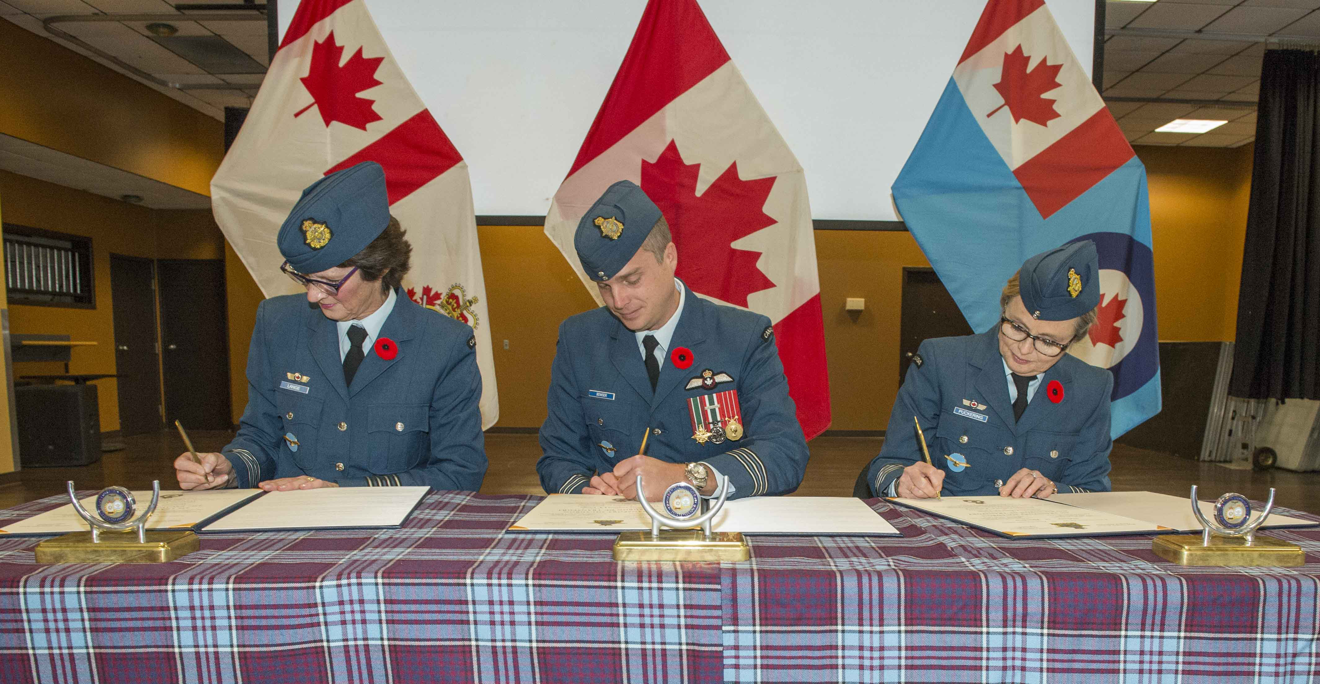 436 Squadron's outgoing honorary colonel, Julie Lange (left), 436 Squadron's commanding officer, Lieutenant-Colonel Andy Bowser, and the squadron's incoming honorary colonel, Cathie Puckering, sign the honorary colonel change of appointment documents during a ceremony at 8 Wing Trenton, Ontario on November 1, 2019. PHOTO: Corporal Rob Stanley, TN08-2019-0412-007