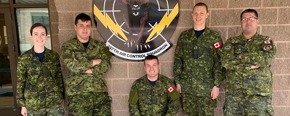 slide - Five people wearing Canadian disruptive pattern combat uniforms stand in a row.