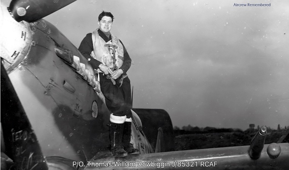 A man wearing flying gear stands on the wing of an aircraft, leaning against the fuselage.