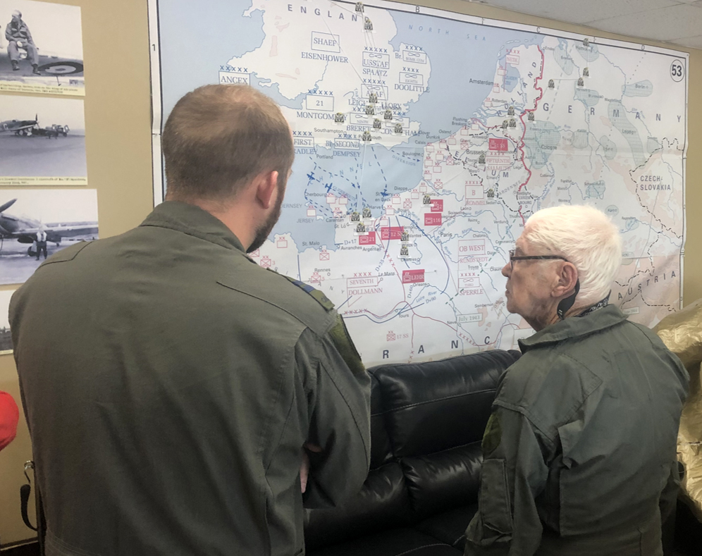 On August 15, 2019, Squadron Leader (retired) Thomas Dowbiggin and a 401 Squadron pilot discuss Squadron Leader Dowbiggin's actions with 401 Squadron during the Second World War. PHOTO: Courtesy 401 Squadron