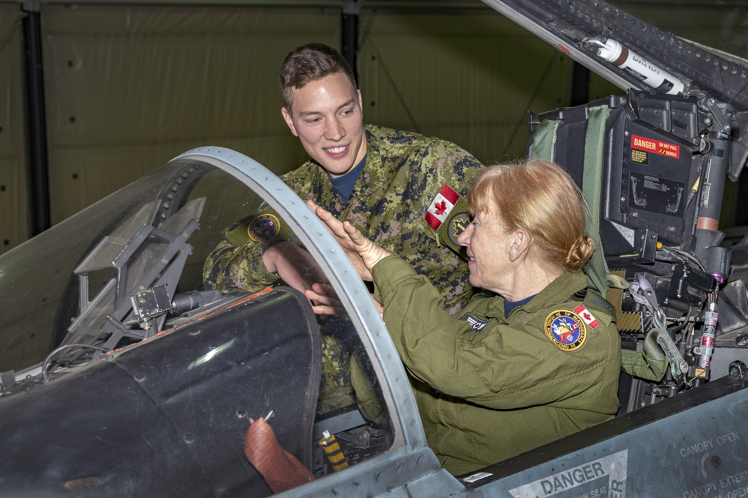 Corporal Benjamin Peddle briefs RCAF Honorary Colonel Loreena McKennitt about the CF-188 Hornet fighter jet on December 14, 2019, during her visit to Air Task Force-Romania at the Mihail Kogӑlniceanu Airbase. PHOTO: Leading Seaman Erica Seymour, RP26-2019-0038-017