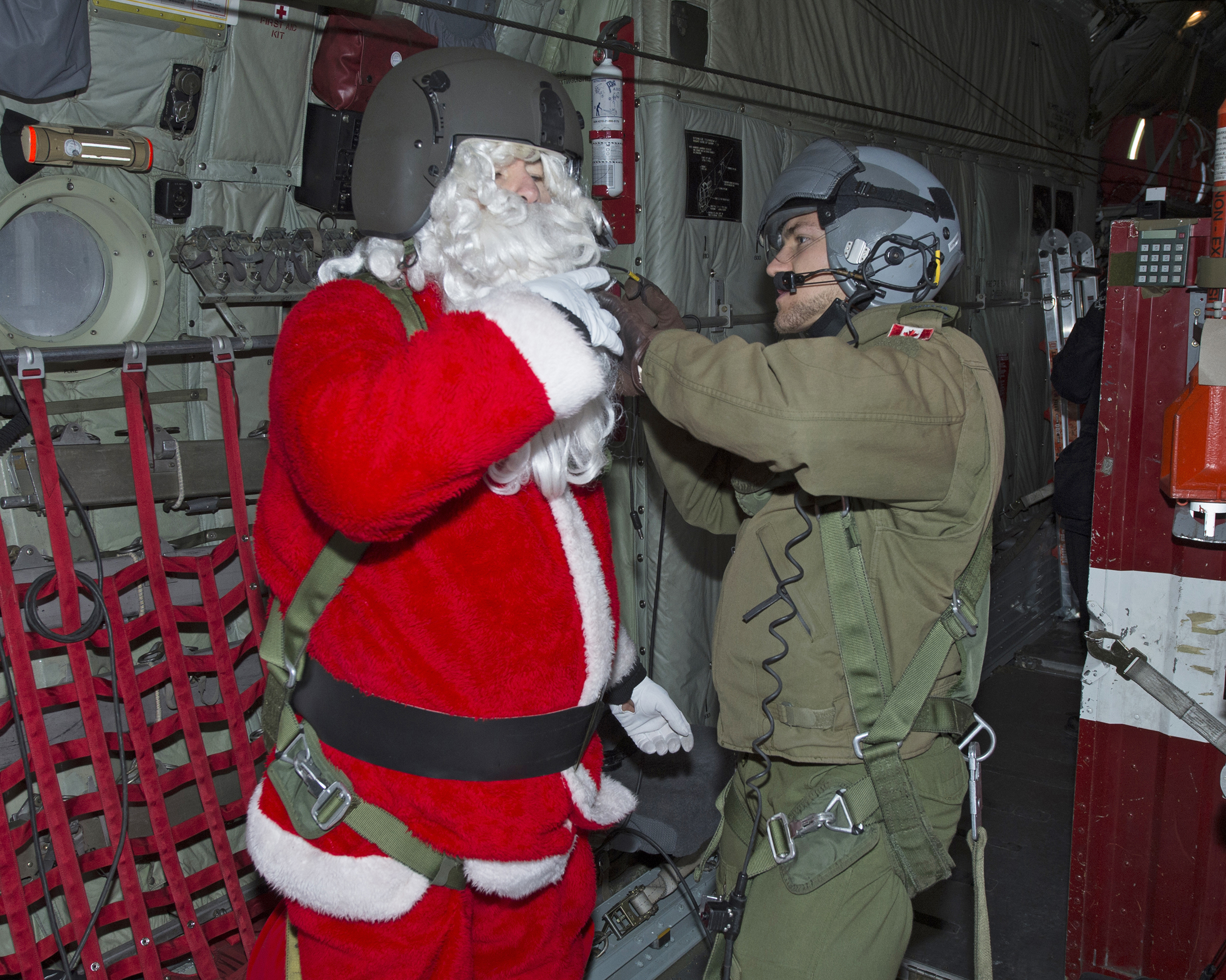 A man wearing a helmet and military flight suit adjusts the helmet worn by a person dressed as Santa Claus inside a large aircraft.