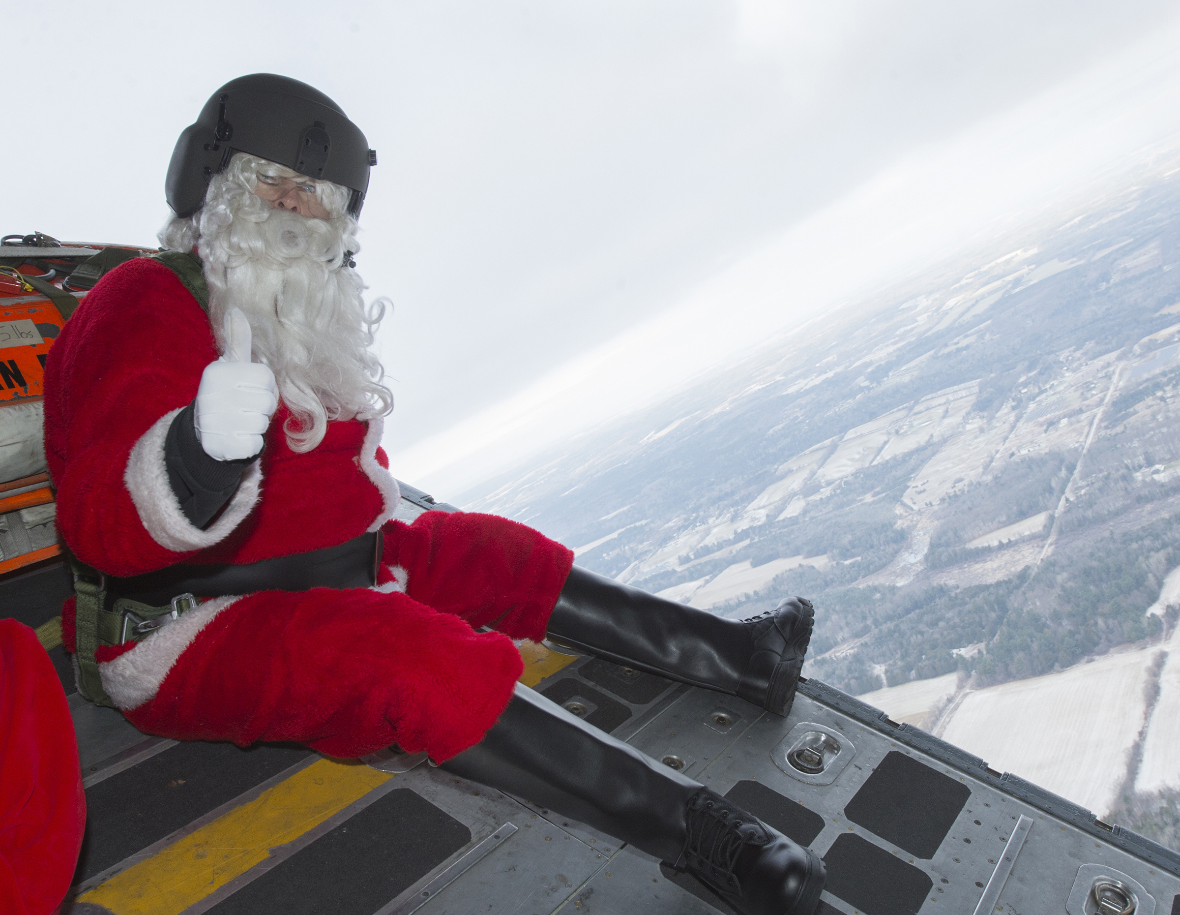 While he doesn't plan on replacing his sleigh and reindeer, Santa gives a thumbs-up to flying on a CC-130H Hercules with aviators from 424 Transport and Rescue Squadron. PHOTO: Leading Seaman Dan Bard, TN09-2018-0441-129