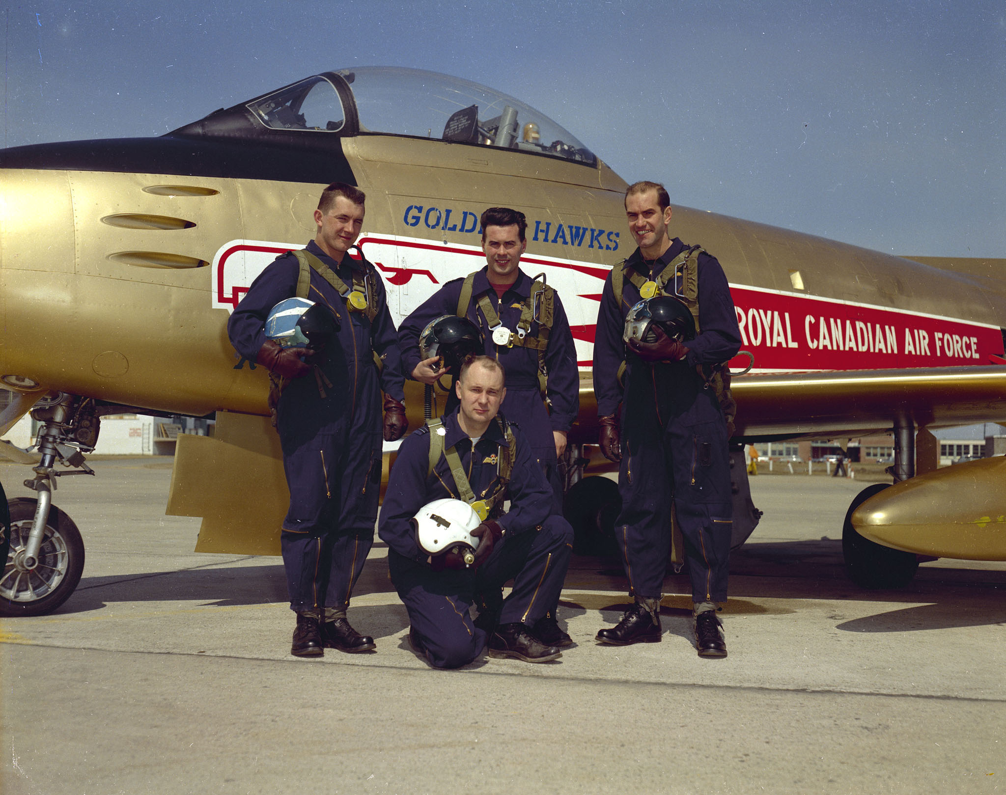 Les membres de l'équipe de voltige de l'ARC, les Golden Hawks : le capitaine d'aviation Jim D. McCombe (à gauche), le capitaine d'aviation G. Jeb Kerr (au centre), le capitaine d'aviation Ed J. Rozdeba et le commandant d'aviation Fern G. Villeneuve (agenouillé). PHOTO : Archives du ministère de la Défense nationale, PCN-126