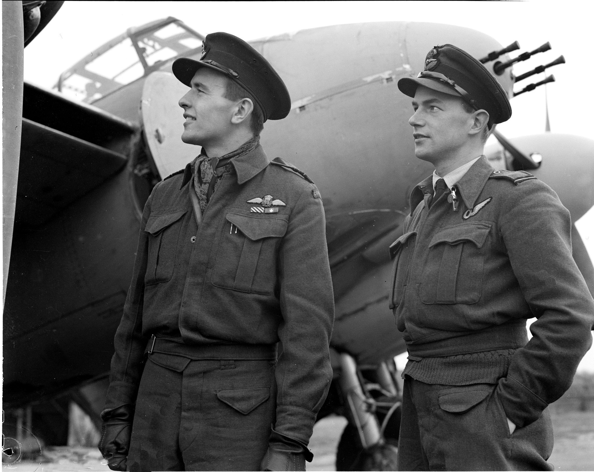 Two men wearing Second World War era air force uniforms, stand in front of a large aircraft.