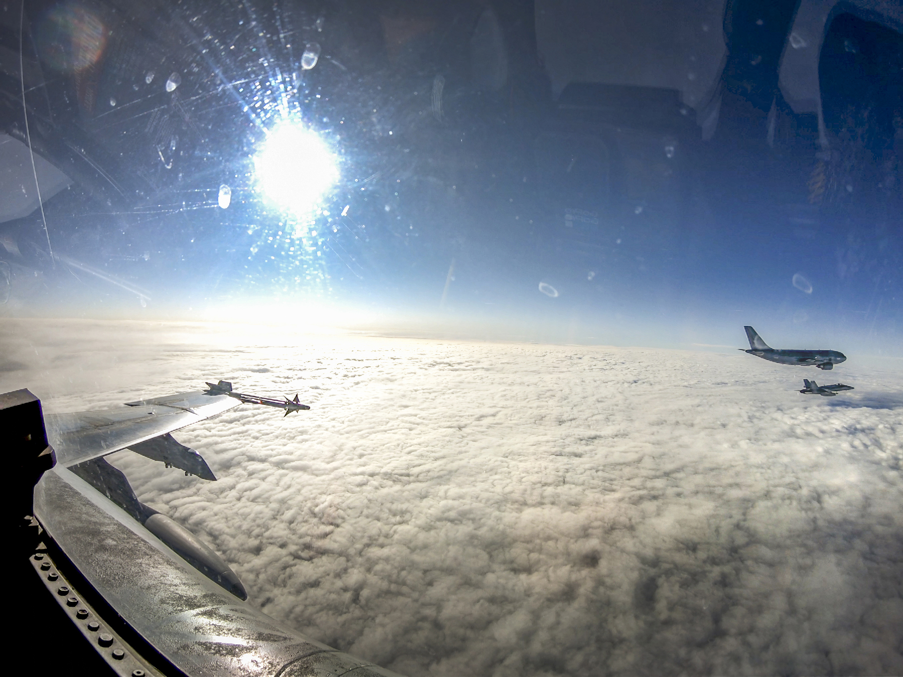 Three aircraft fly in formation in a blue sky under a bright sun above the cloud cover.