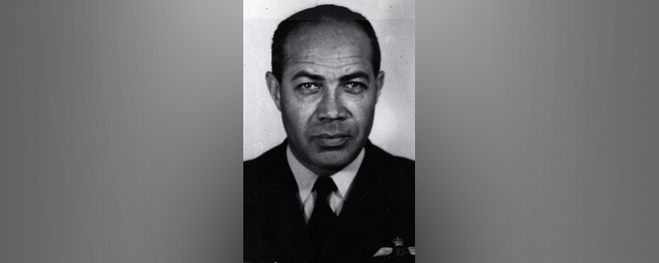 slide - A black and white photo of a black man wearing a shirt and tie, and a uniform jacket with wings.