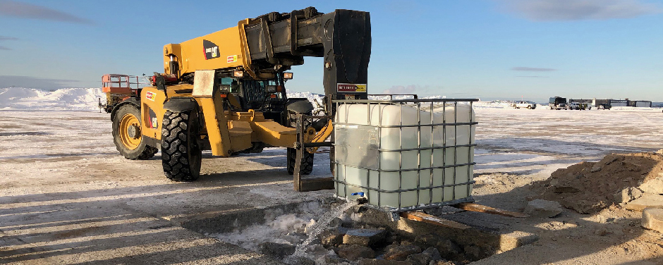 slide - In winter, a large yellow construction-type vehicle pours water into a shallow, rectangular hole filled with stone debris.