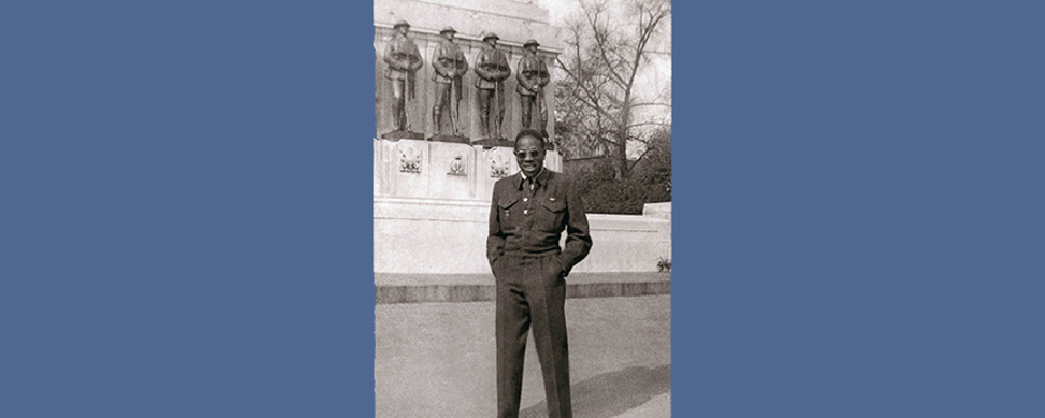 slide - In a black-and-white photograph, a Black man wearing a uniform stands with his hands in his pockets in front of a large memorial displaying statues of men in uniforms.