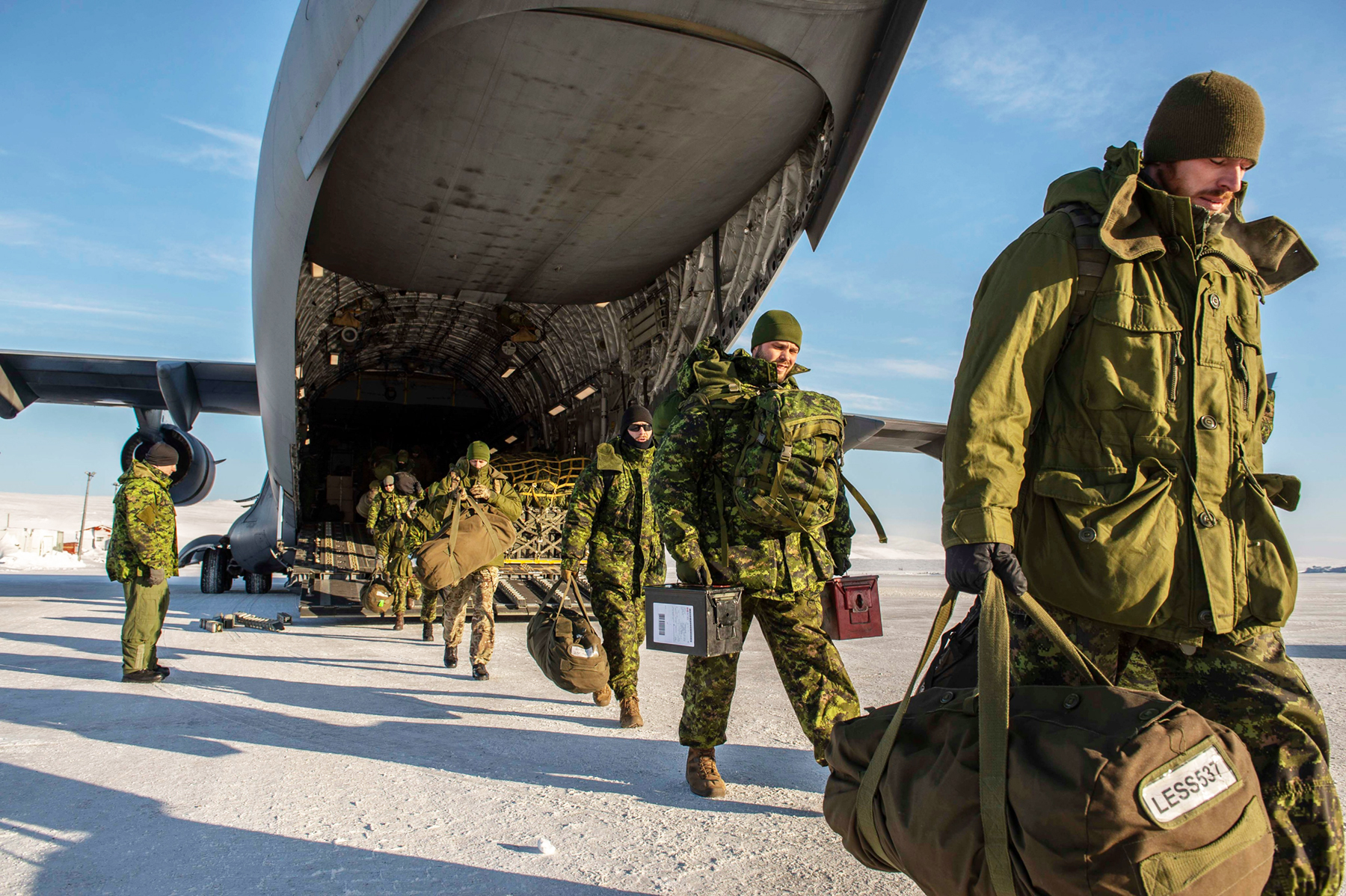 People wearing disruptive pattern uniforms and carrying a variety of bags and gear disembark a large cargo aircraft on a packed snow runway.