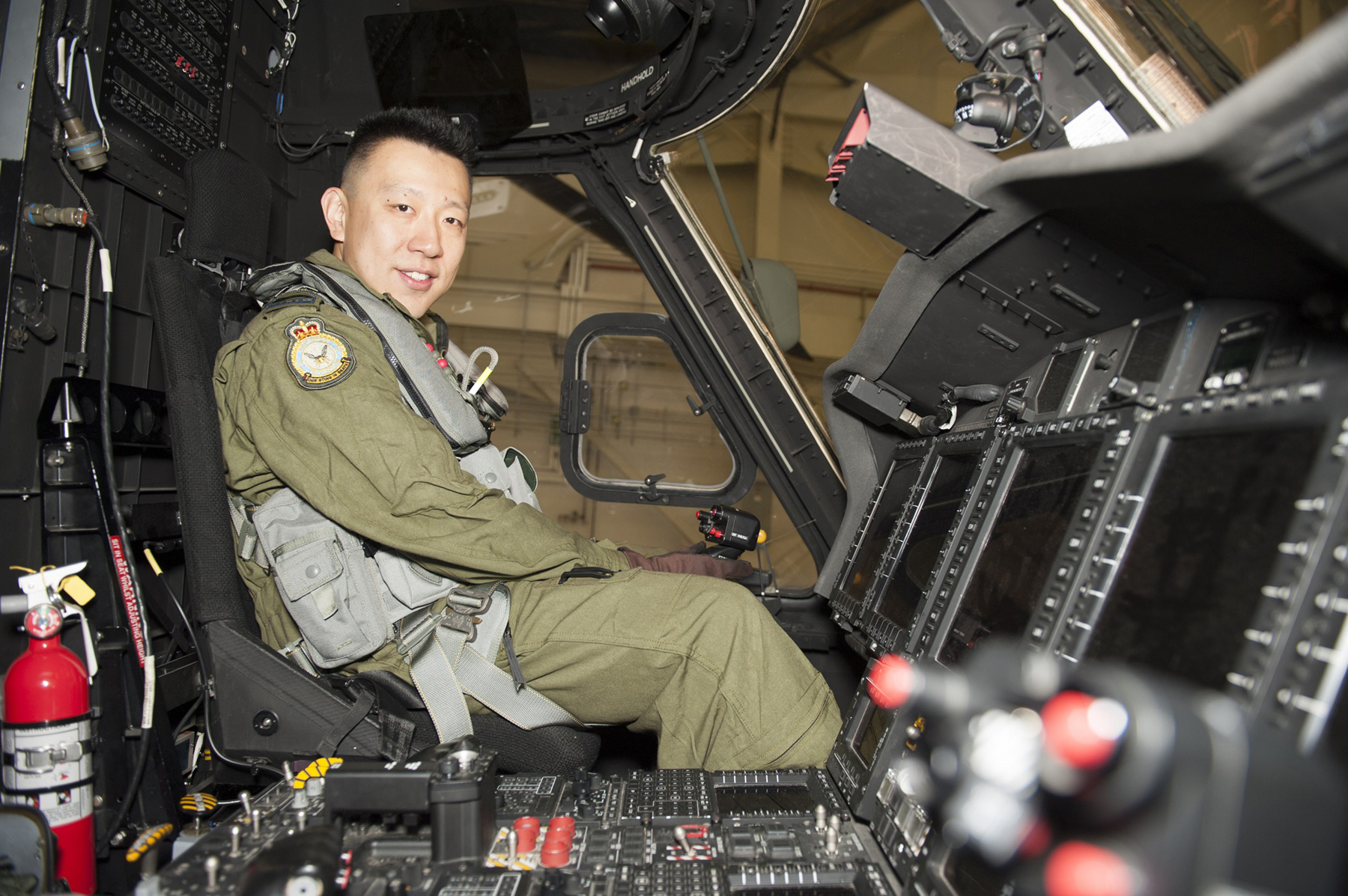 A man wearing an olive green flight suit sits in the cockpit of a helicopter.