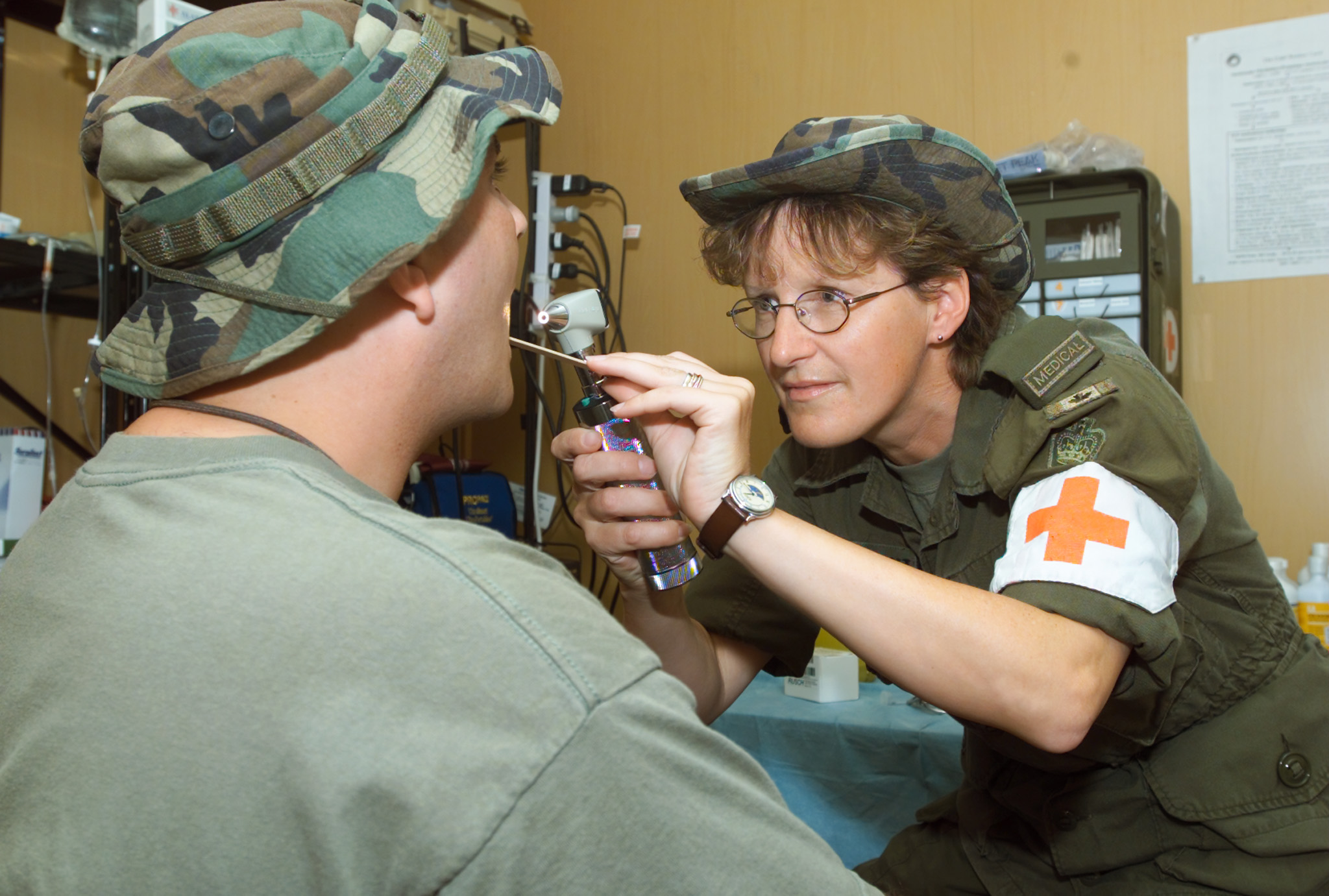 On February 12, 2002, Warrant Officer Dianne Maidment, a physician's assistant from 14 Wing Greenwood, Nova Scotia, checks a patient's throat in a medical clinic in the Arabian Gulf region, during Operation Apollo. PHOTO: Master Corporal Jeff D. de Molitor, APD02-0009a-01