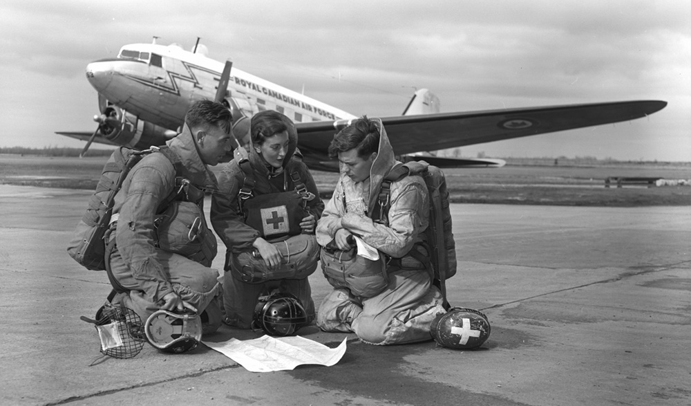 In this undated photo, Para Rescue Team 29811—Leading Aircraftman C.L. Hegadorne, Flying Officer (Nursing Sister) E.R. Kelly and Corporal R.E. Crawford—study a map before take-off. PHOTO: DND Archives, PL-87049