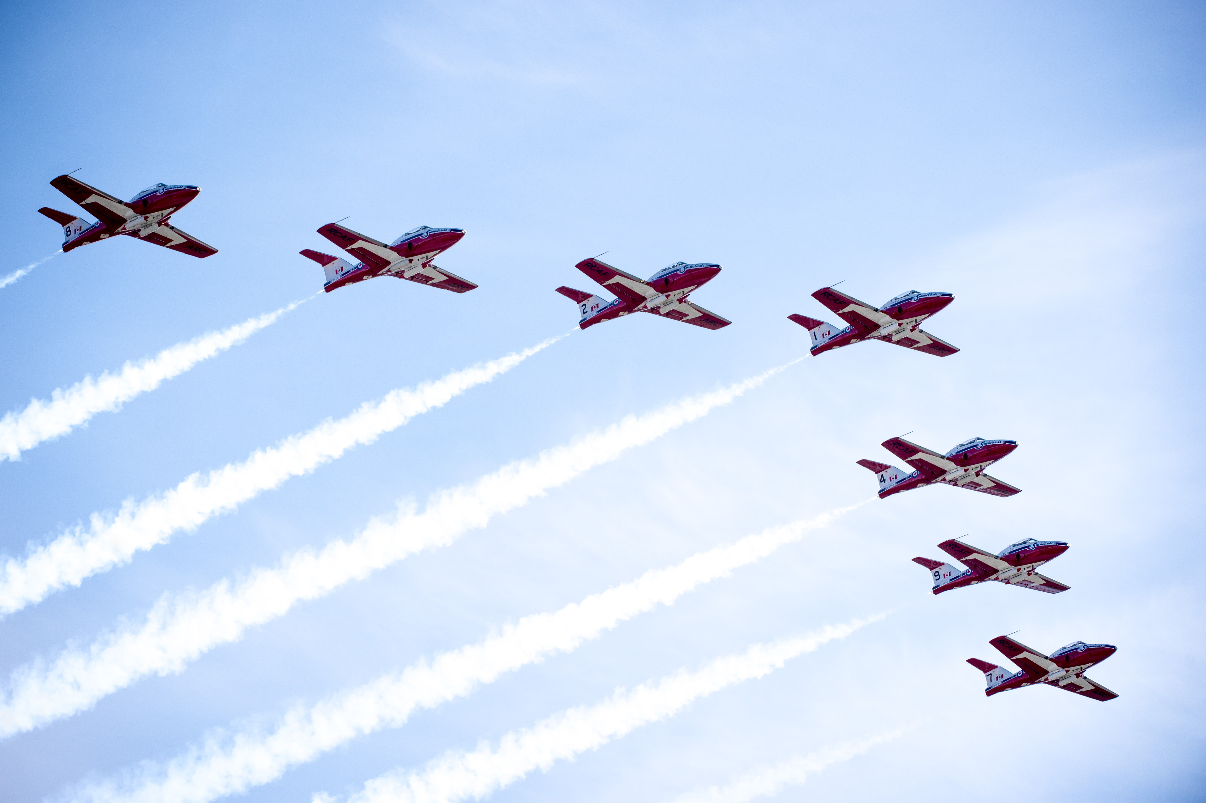 Seven red and white jet aircraft fly in formation.