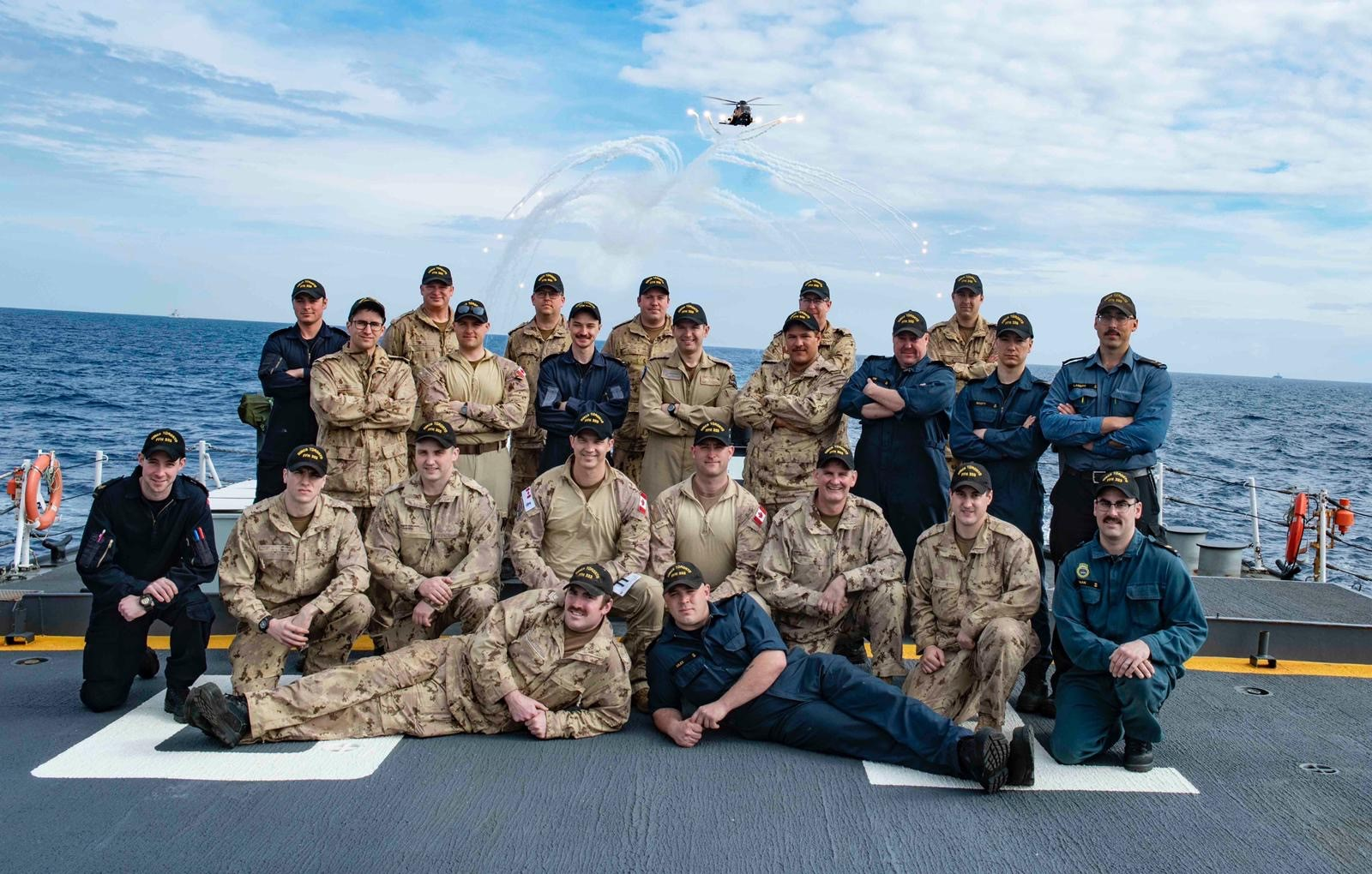 Maj Matthew Dukowski (fourth from left, front row kneeling), Helicopter Air Detachment Commander, pictured with members of the air detachment on HMCS Toronto, with a CH-148 Cyclone flying above, during a six-month deployment on Operation Reassurance in 2019. PHOTO: Submitted