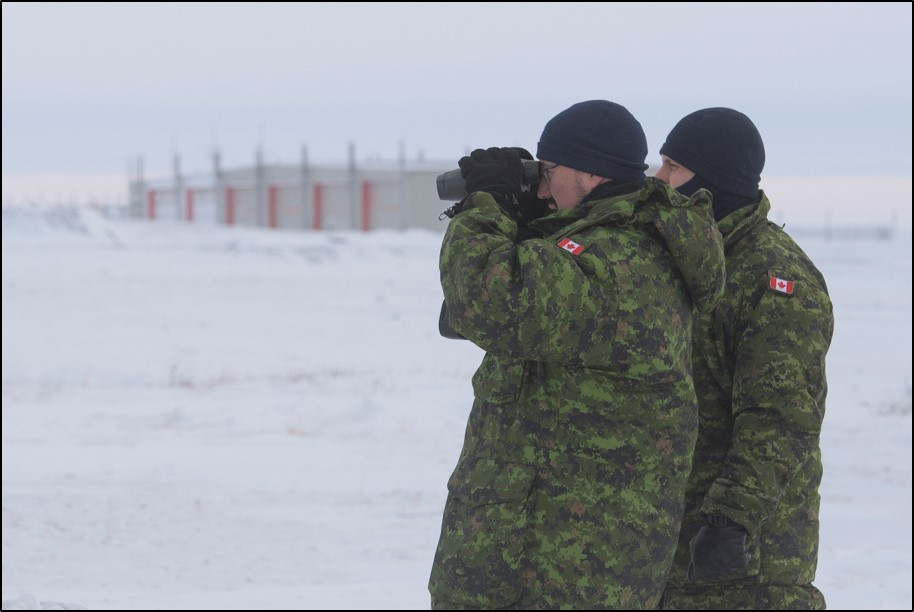 Two people wearing camouflage uniforms standing in snow use binoculars.
