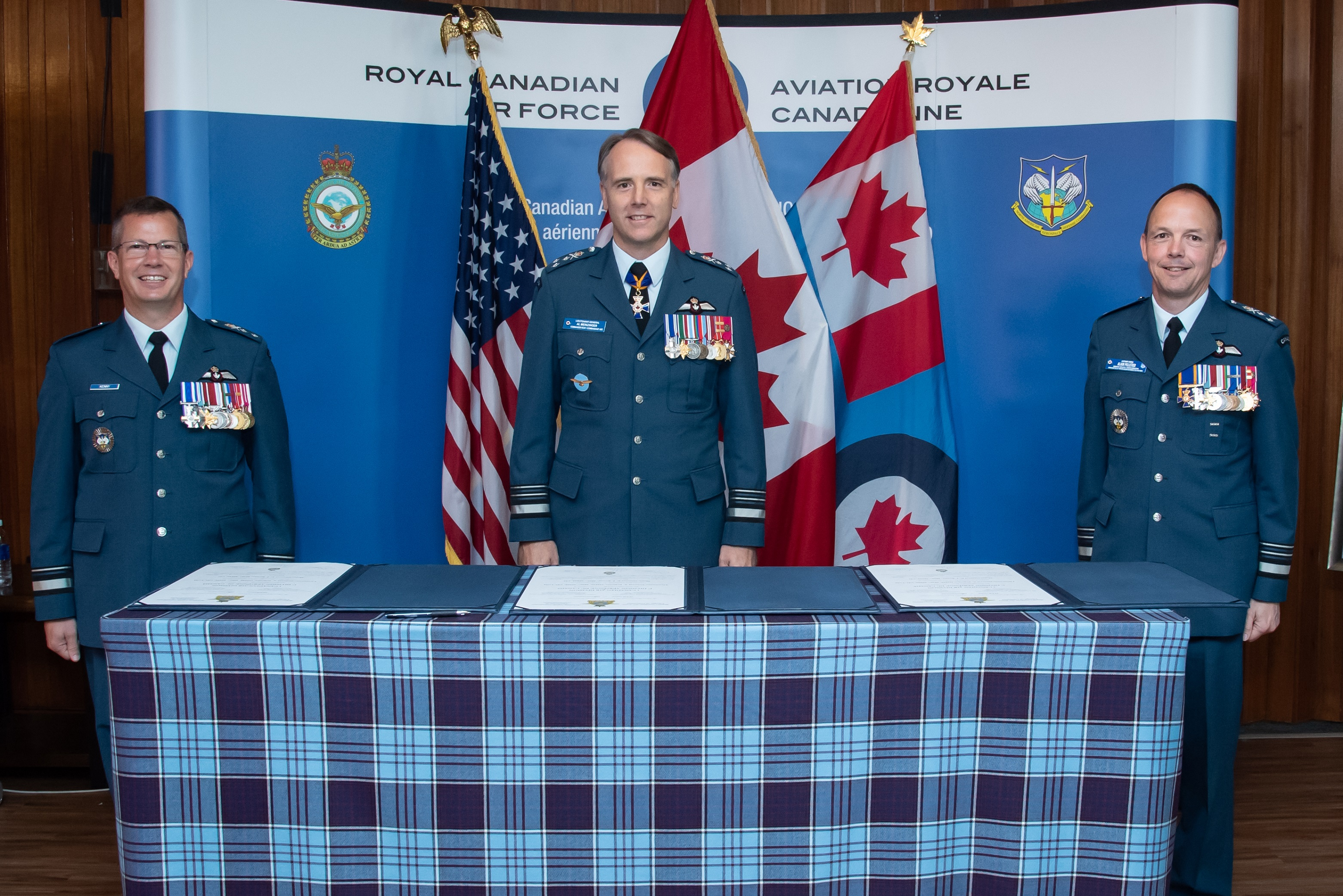Three men wearing blue military uniforms stand behind a table covered in tartan and on which are documents. Behind the men, are a big blue and white backdrop and three flags.