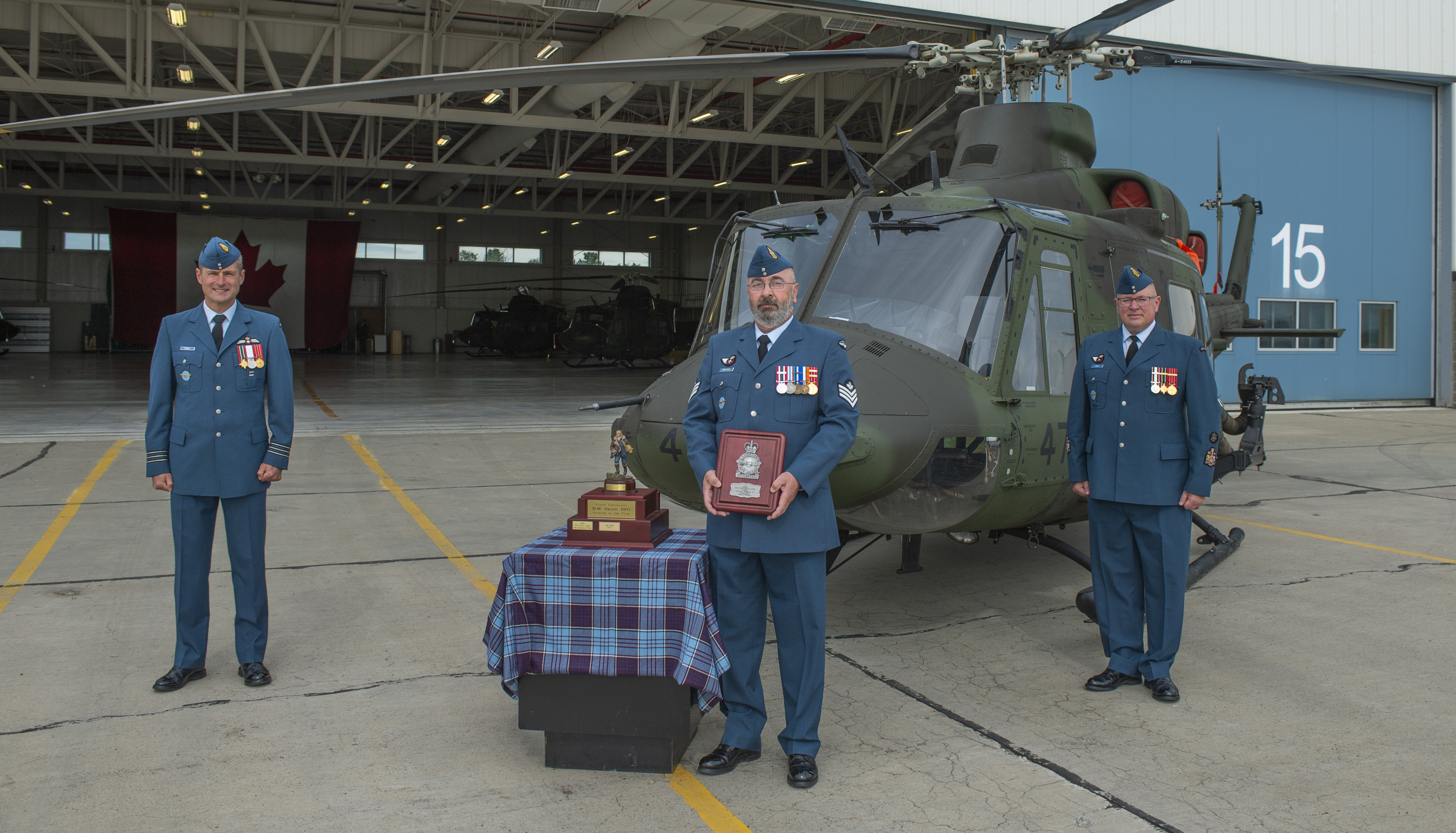 Three men wearing blue military uniforms and wedge hats stand outside a hangar in front of a military helicopter. The man in the middle holds a plaque and beside him is a little table with a trophy.