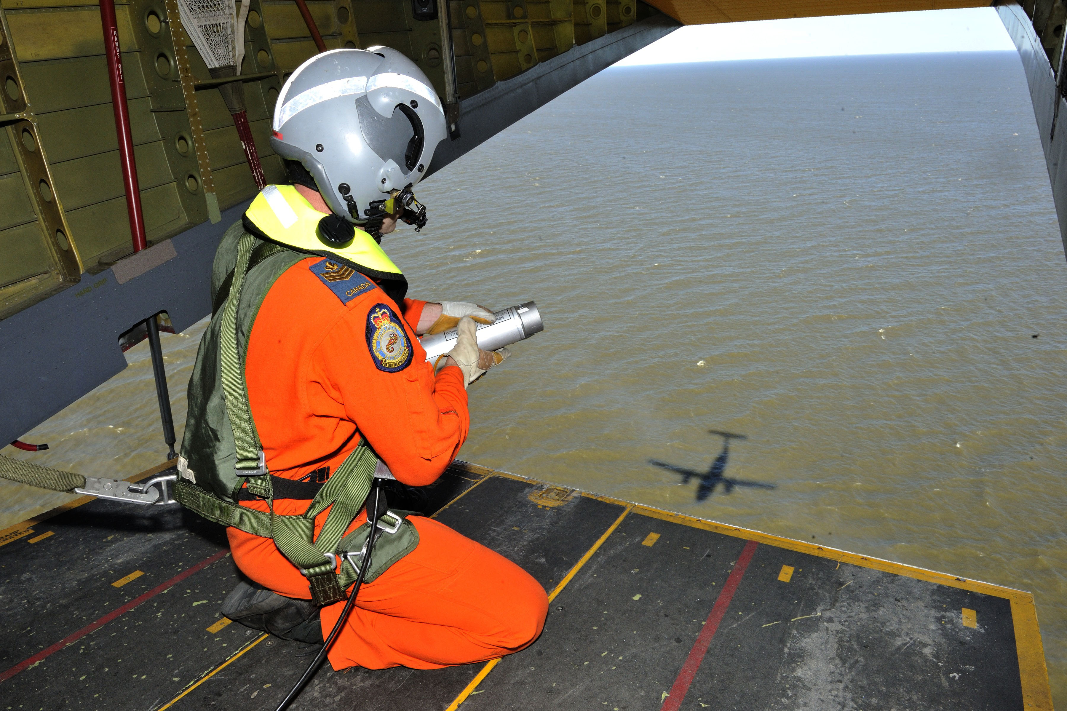 A man wearing an orange jump suit and a grey helmet holding a grey canister kneels on the open ramp of an aircraft flying over water.