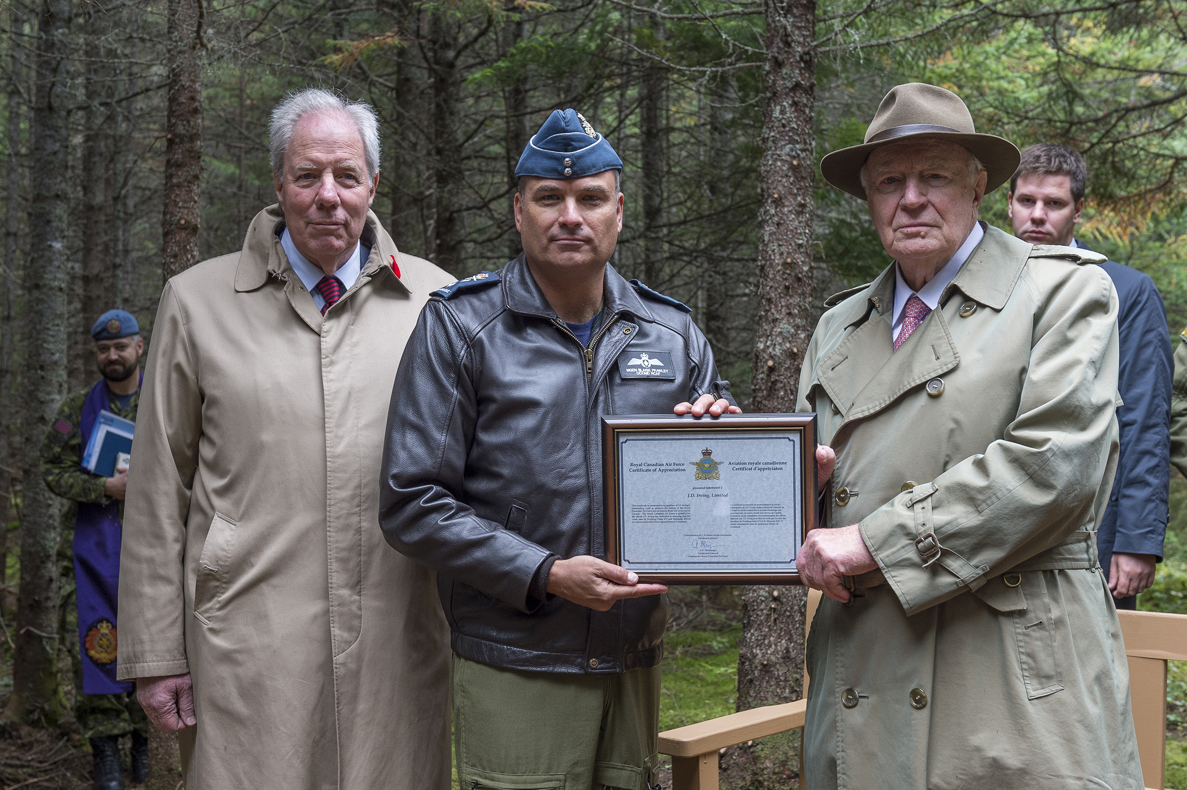 Major-General Blaise Frawley (centre) presents a certificate of appreciation to Mr. J.K. Irving (right) and Mr. Jim Irving of J.D Irving, Limited during the ceremony commemorating Warrant Officer Class 2 James Edward Doan and Corporal David Alexander Rennie who died on September 14, 1939, when their Northrop Delta aircraft crashed near Plaster Rock, New Brunswick. PHOTO: Corporal Nicolas Alonso, GN02-2019-0949-020