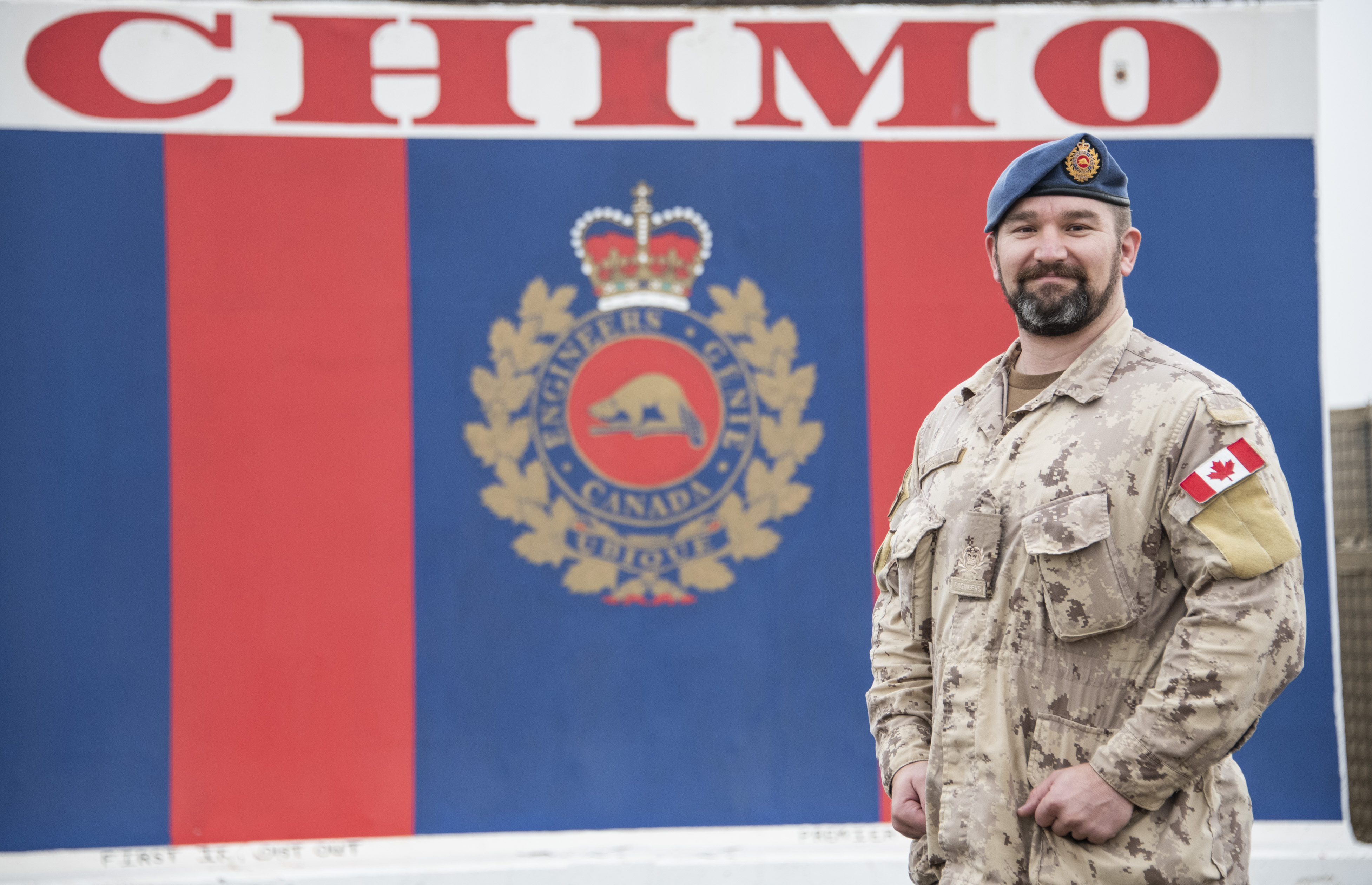 "A man wearing a combat uniform stands in front of a wall with vertical blue and red stripes, the Canadian Armed Forces' engineers' crest and the word ""CHIMO""."