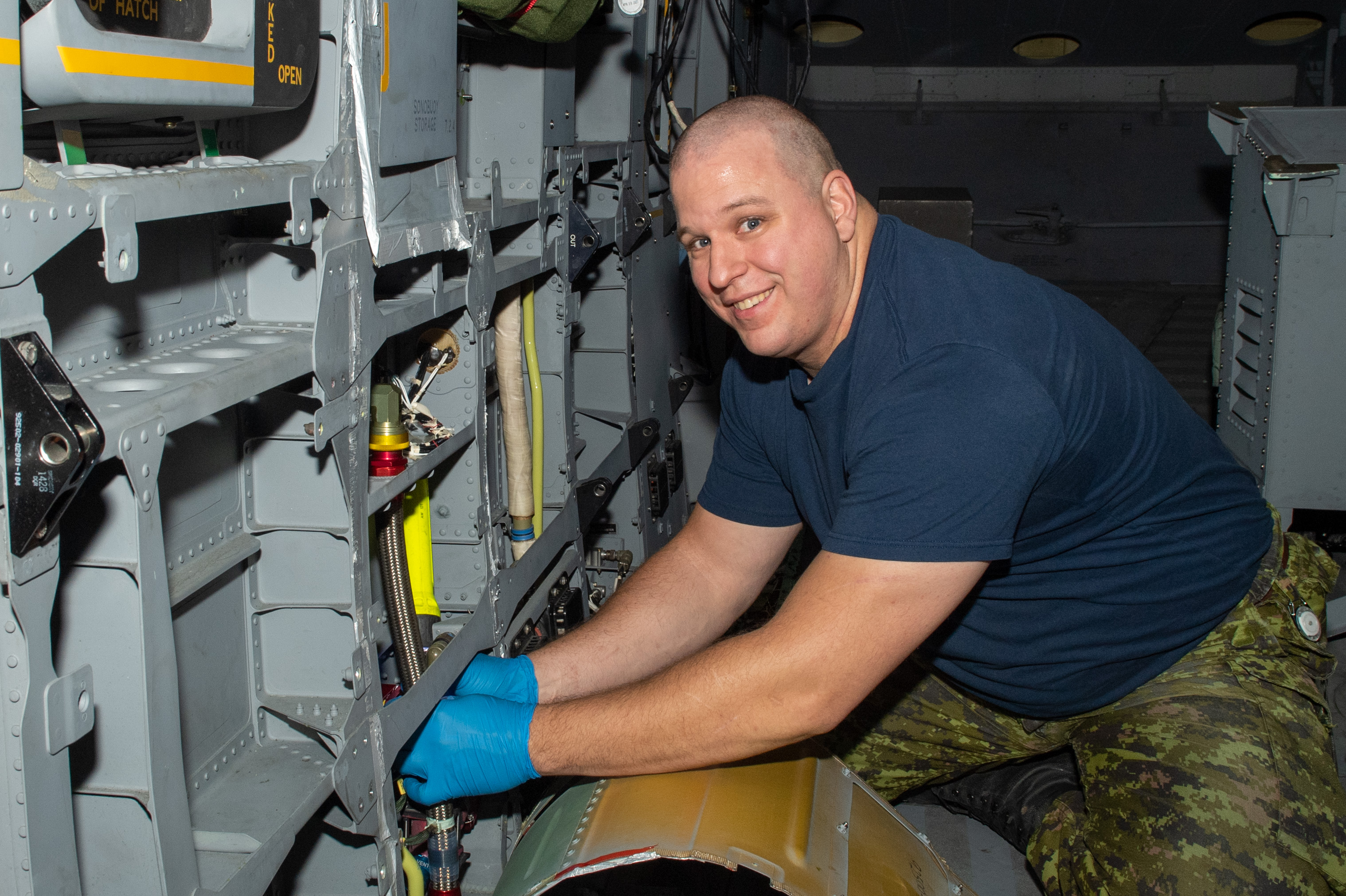 A smiling man wearing a dark blue t-shirt and camouflage pants works on a helicopter.