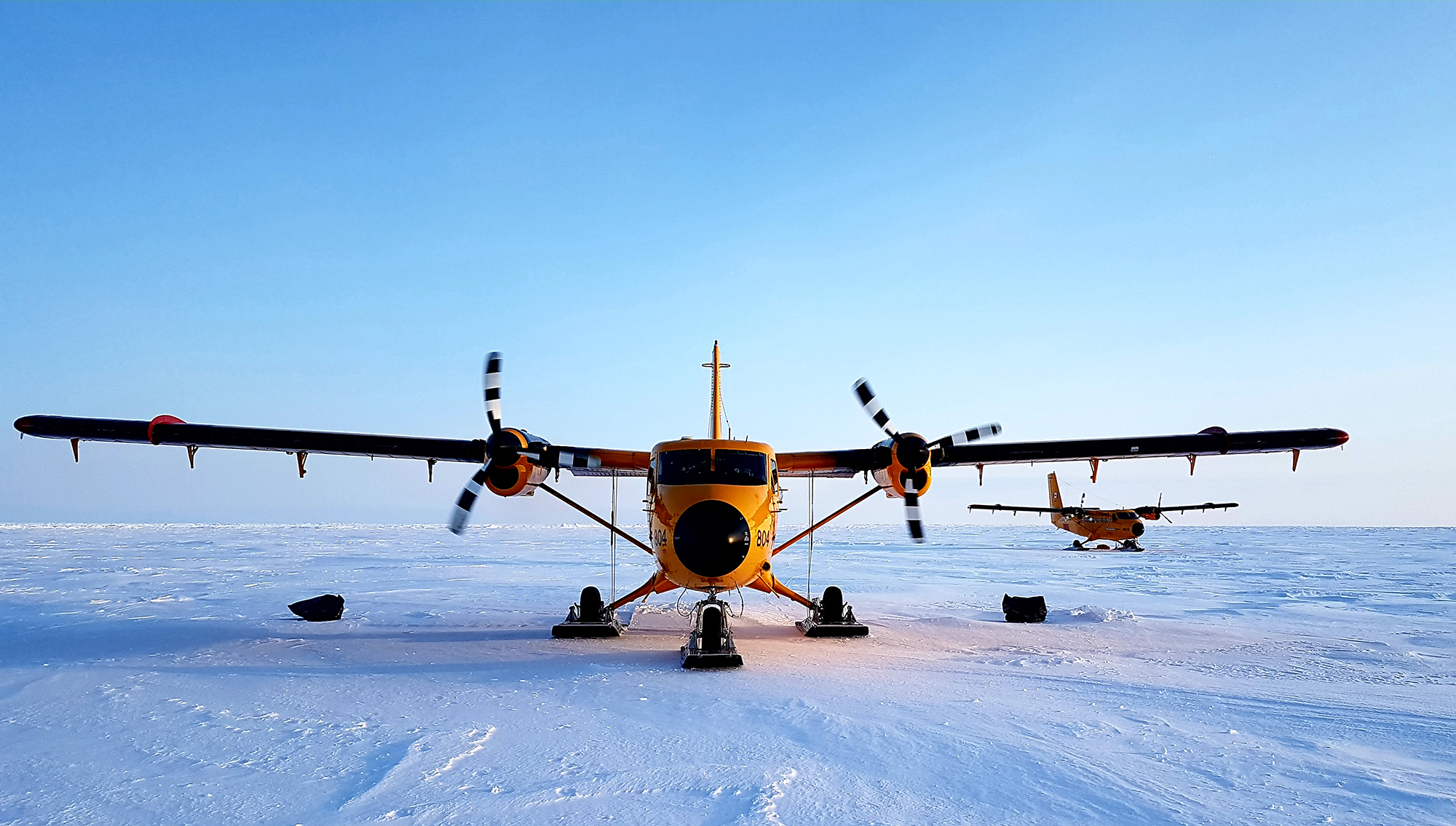 Two orange twin-propeller aircraft equipped with skis on snow in the Arctic.