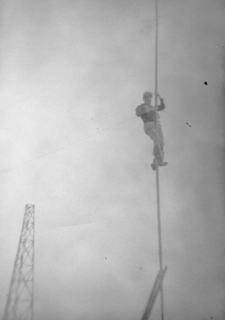 Cpl Bauld climbs a pole to change the windsock – the only instrument the weather team had at Cape Bauld to measure wind speed and direction. PHOTO: courtesy Bill Lloyd.