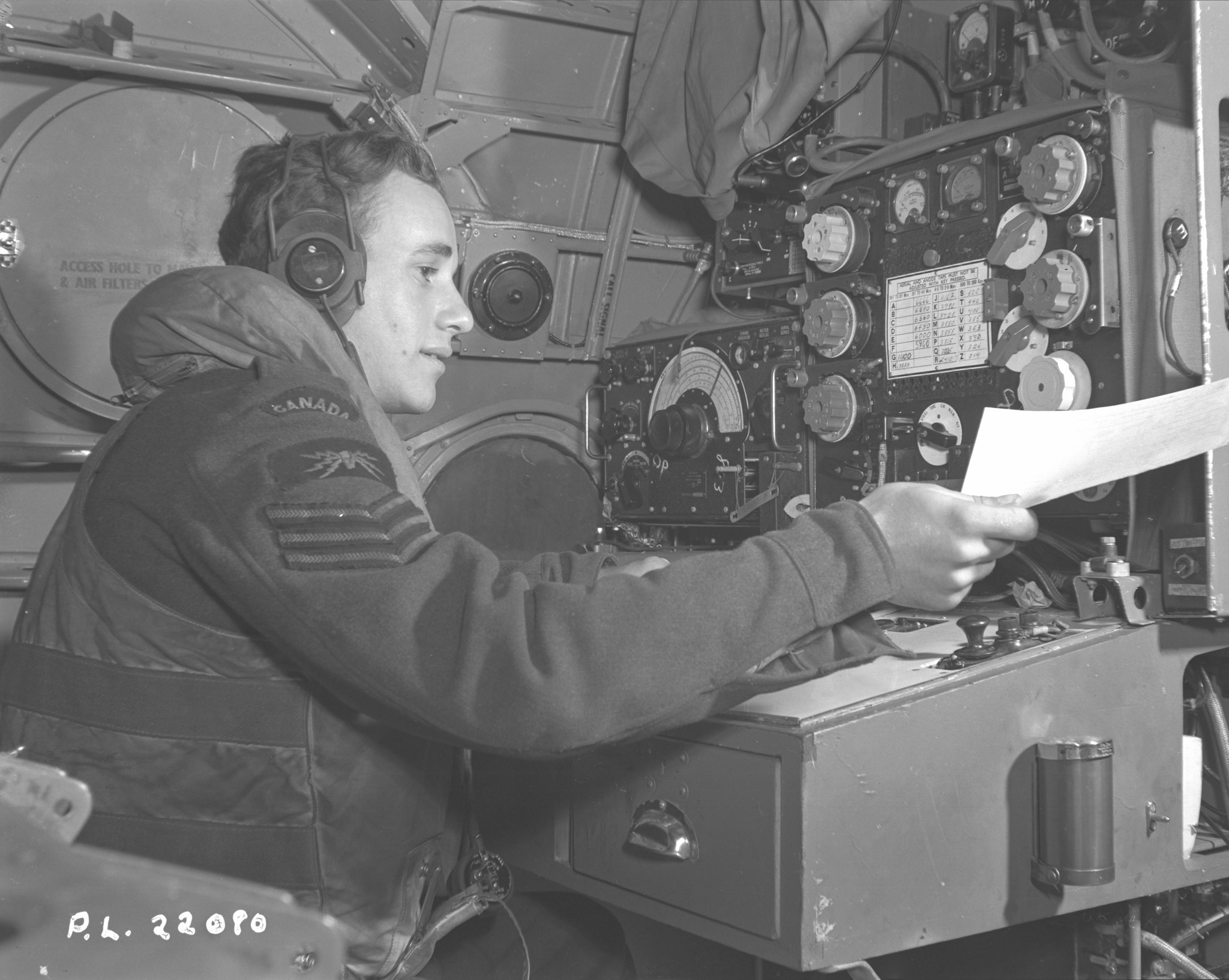 Sergeant L.J. Irving, a wireless operator onboard a Sunderland flying boat from the RCAF's 423 Squadron, part of Coastal Command, hands a message to his skipper during an anti-submarine patrol. PHOTO: DND Archives, PL-22080
