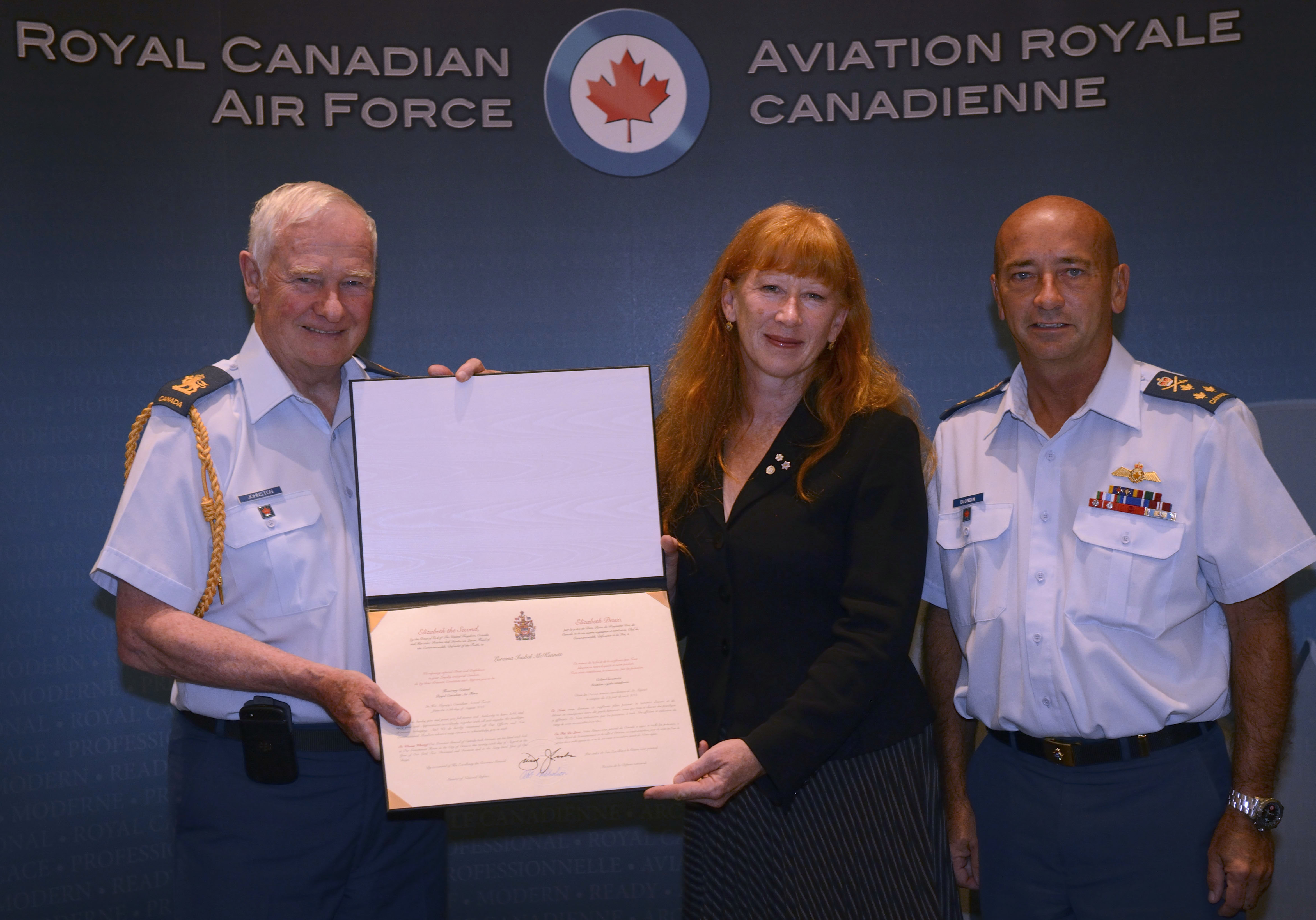 His Excellency the Right Honourable David Johnston, Governor General and Commander-in-Chief of Canada (left), presents Ms Loreena McKennitt with a scroll marking her appointment as the new honorary colonel of the Royal Canadian Air Force alongside Lieutenant-General Yvan Blondin, the commander of th