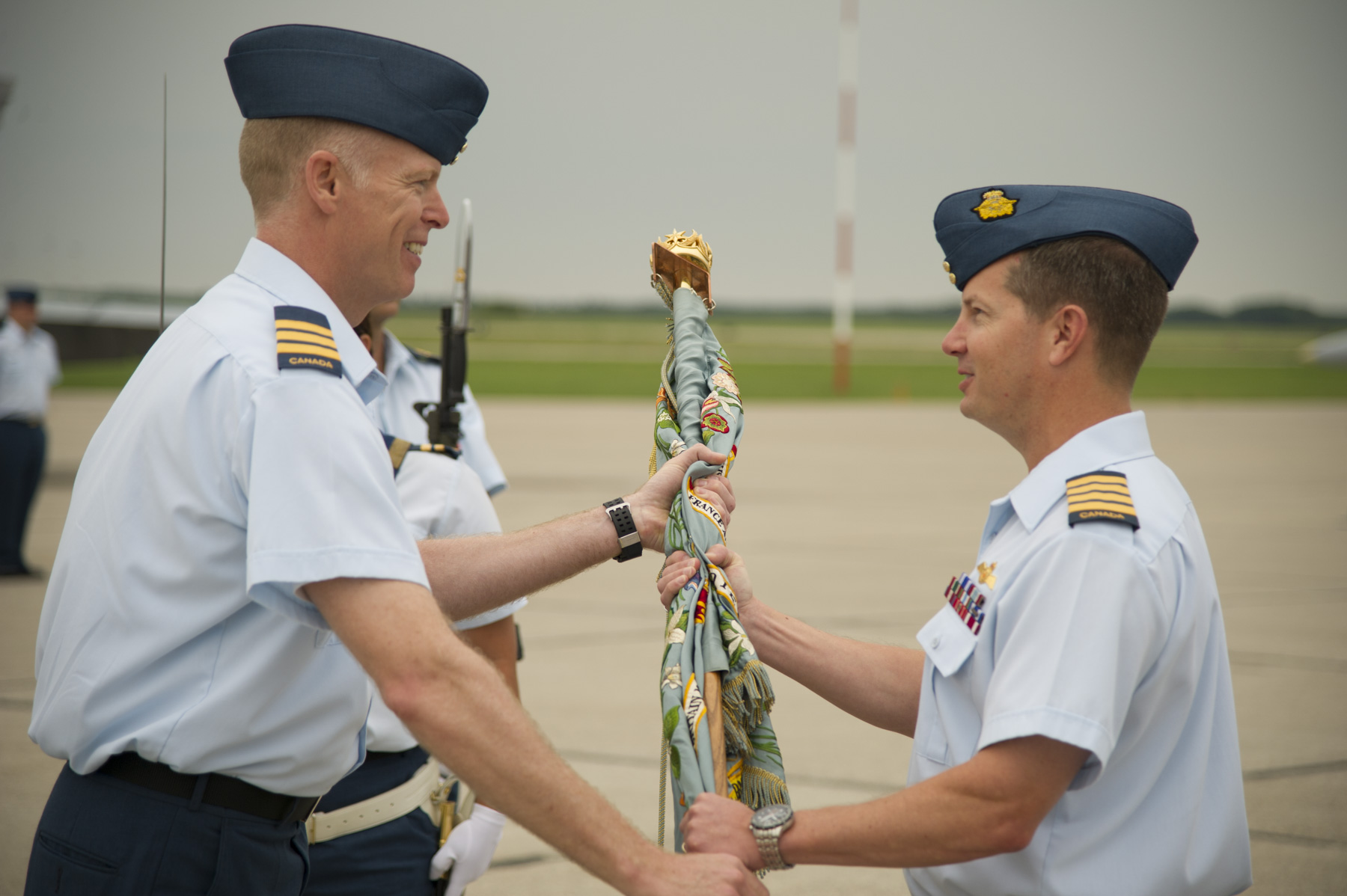 Colonel Eric Kenny (right) presents 401 Tactical Fighter Squadron's Colour to the squadron's commanding officer, Lieutenant-Colonel Joseph Mullins during a ceremony to re-activate the squadron on June 30, 2015. PHOTO: Corporal Patrick Drouin