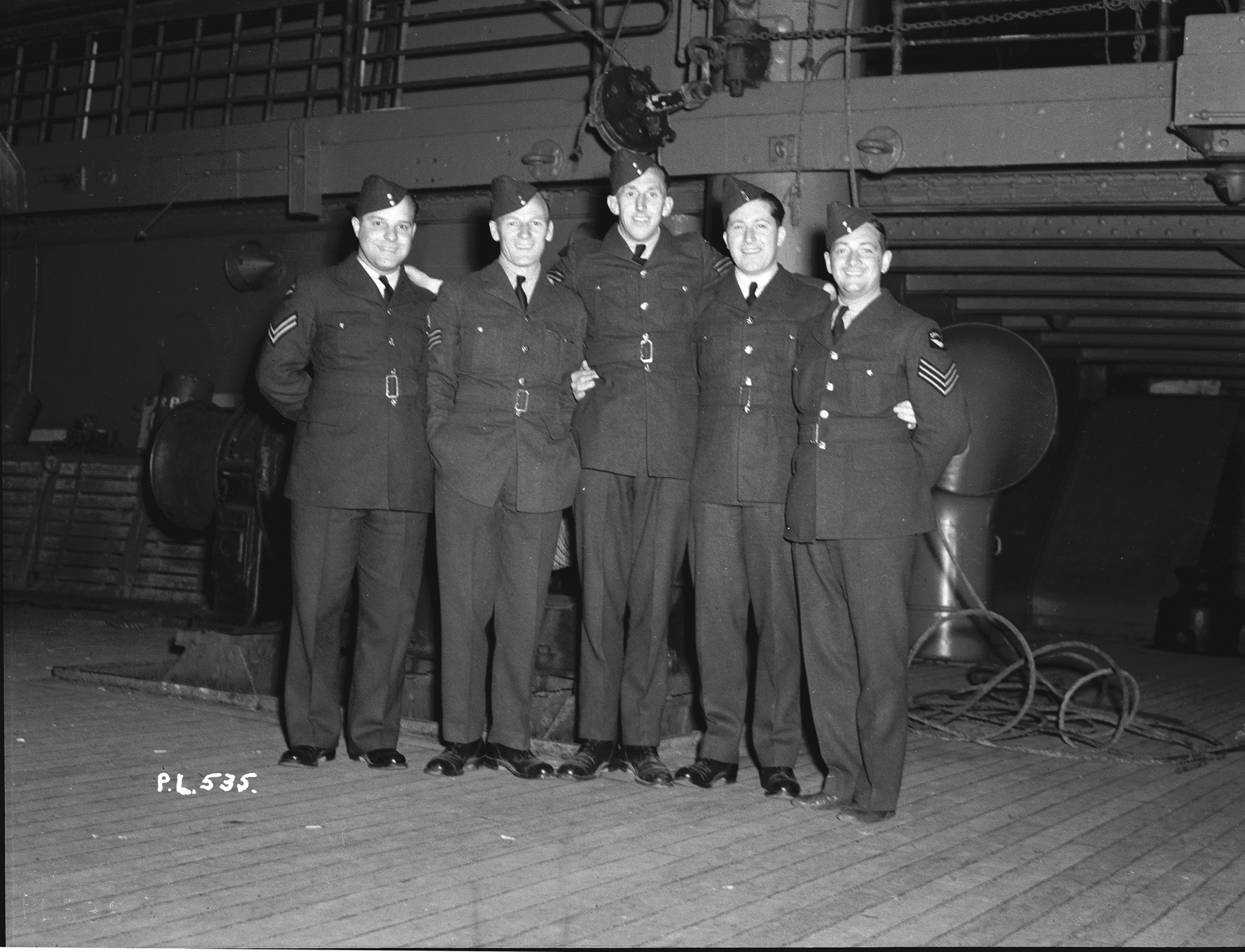 "The original caption of this photo reads ""Several non-commissioned officers of the RCAF's No. 1 (Fighter) Squadron adopted a member of the overseas headquarters staff before departing for active service overseas. The group includes one of the oldest and one of the youngest members of the unit: Sergeant John Burdes having been with this squadron for nine years, while Flight Sergeant Saunders was transferred from another squadron less than 24 hours before sailing. In this photo, taken on June 8, 1940, are (left to right) Corporal A.L.P. Gagnon of St. Boniface, Manitoba; Flight Sergeant L.G. Saunders of Ottawa, Ontario; Sergeant John R. Burdes of New Westminster, British Columbia; Sergeant-major A.C. Wilson of Ottawa, Ontario, who was sailing to join the Overseas Headquarters of the RCAF in England; and Sergeant F. Worrell of Montreal, Quebec."" PHOTO: DND Archives, PL-535"