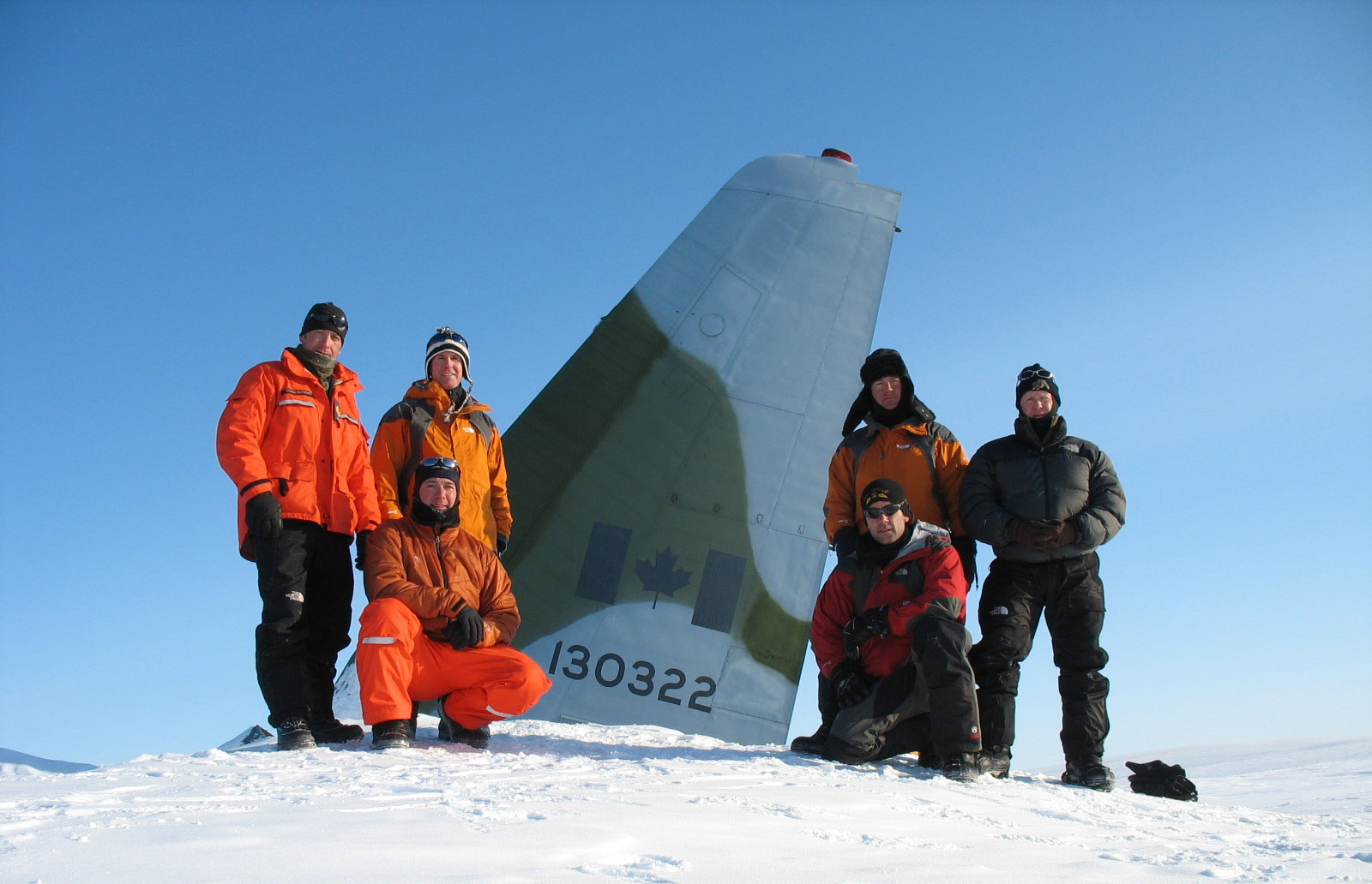 In April 2008, six search and rescue technicians from 14 Wing Greenwood, Nova Scotia, participated in a two-week survival course near Canadian Forces Station Alert. During their time on Ellesmere Island, the team honoured the memory and heroism of those who died in the October 1991 crash of a CC-130 Hercules near Alert, and the subsequent rescue efforts of determined search and rescue technicians. Here they visit the crash site, where the tail of the Hercules protruded above the spring snow cover. Front row (left to right) Master Corporal André Bergeron and Sergeant Dan Villeneuve; back row (left to right) Sergeant Sean MacEachern, Warrant Officer Keith Mitchell, Master Corporal Rob Hardie and Master Corporal Dan Bodden. PHOTO: Courtesy Warrant Officer Keith Mitchell